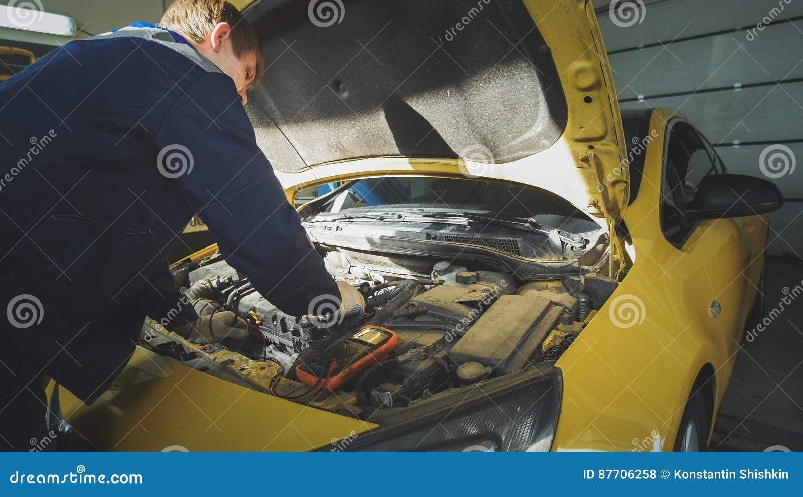 Caucasien de mécanicien dans le service de voiture - réparant en compartiment réacteur