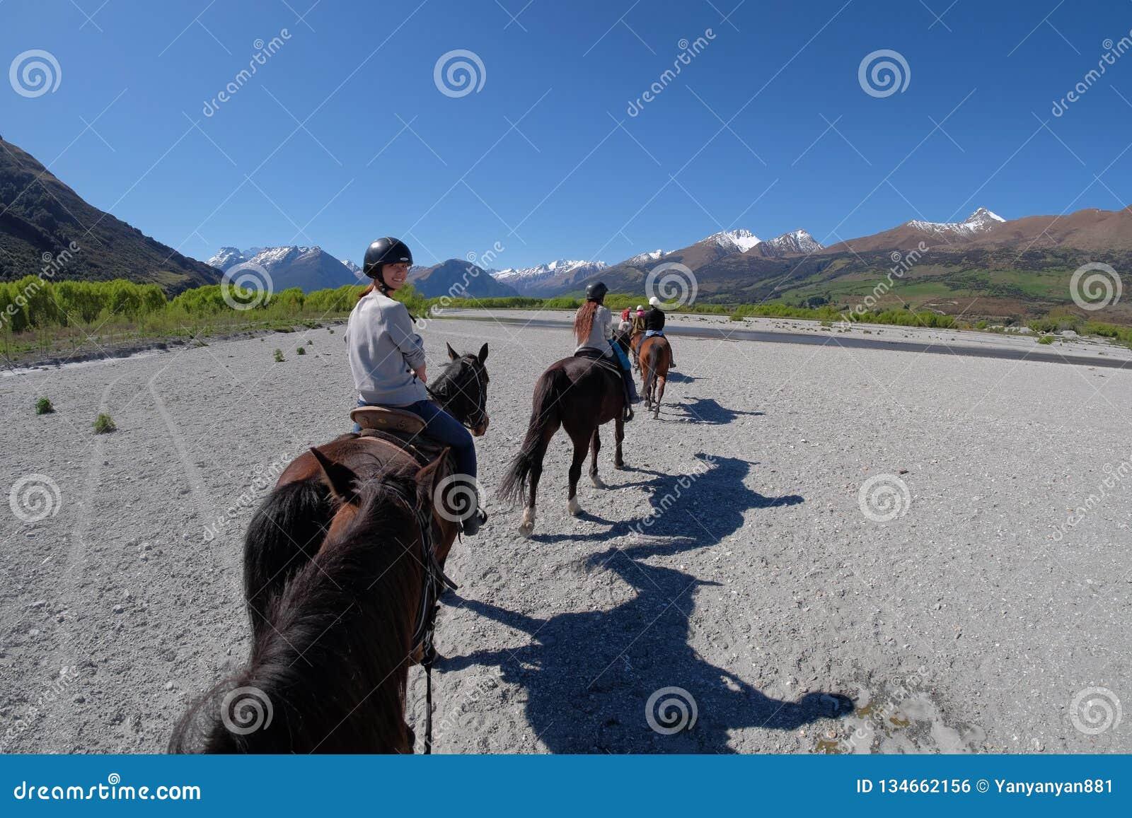 Cauce del río seco de la travesía de la muchacha en caballo en Nueva Zelanda