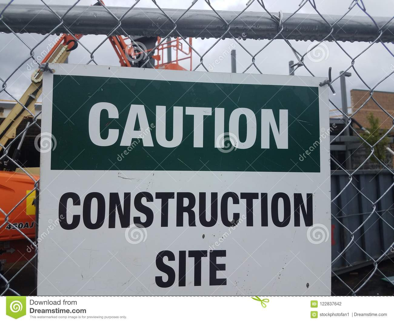 Caution construction site sign on metal fence