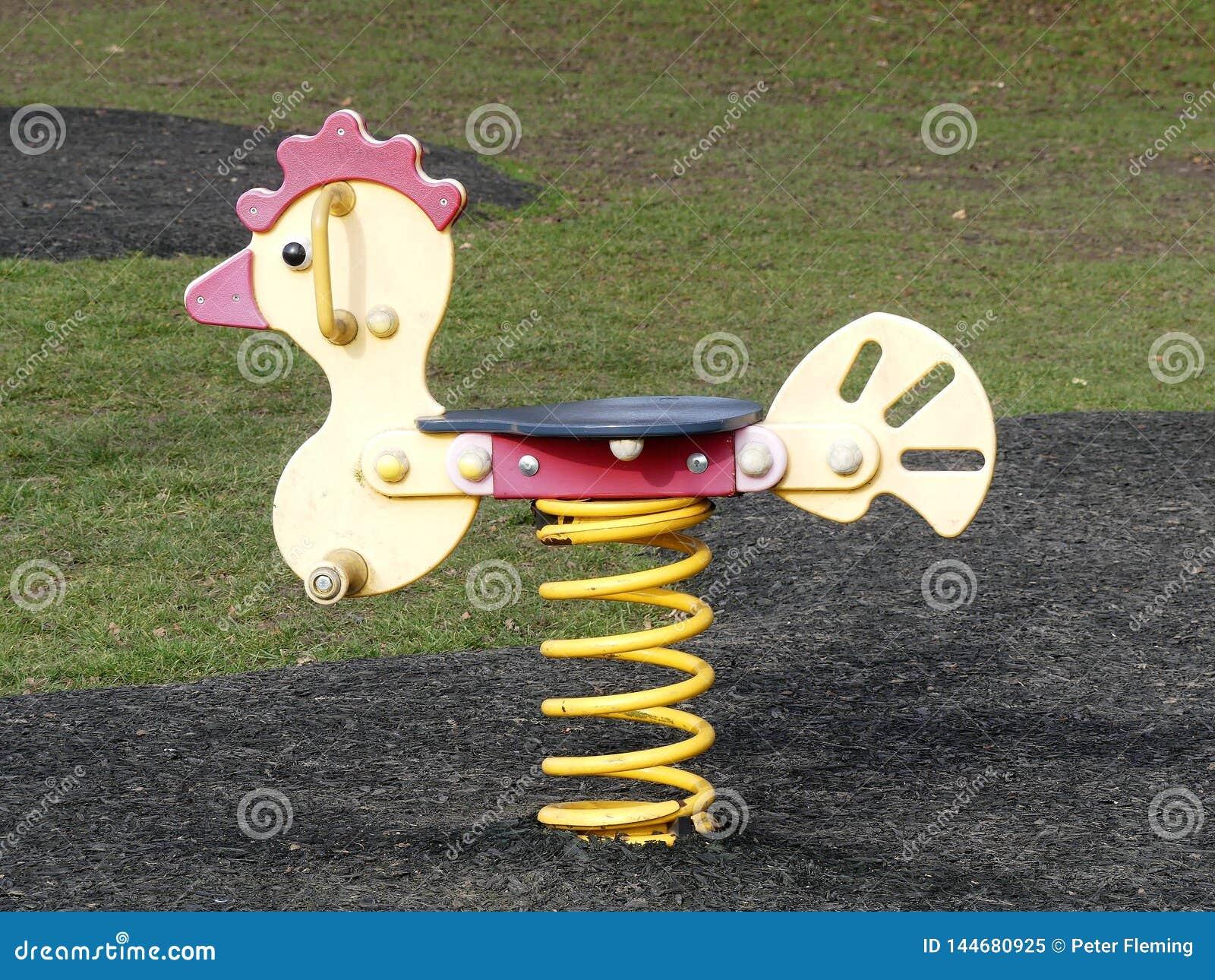 Cavaleiro amarelo da mola no campo de jogos das crianças