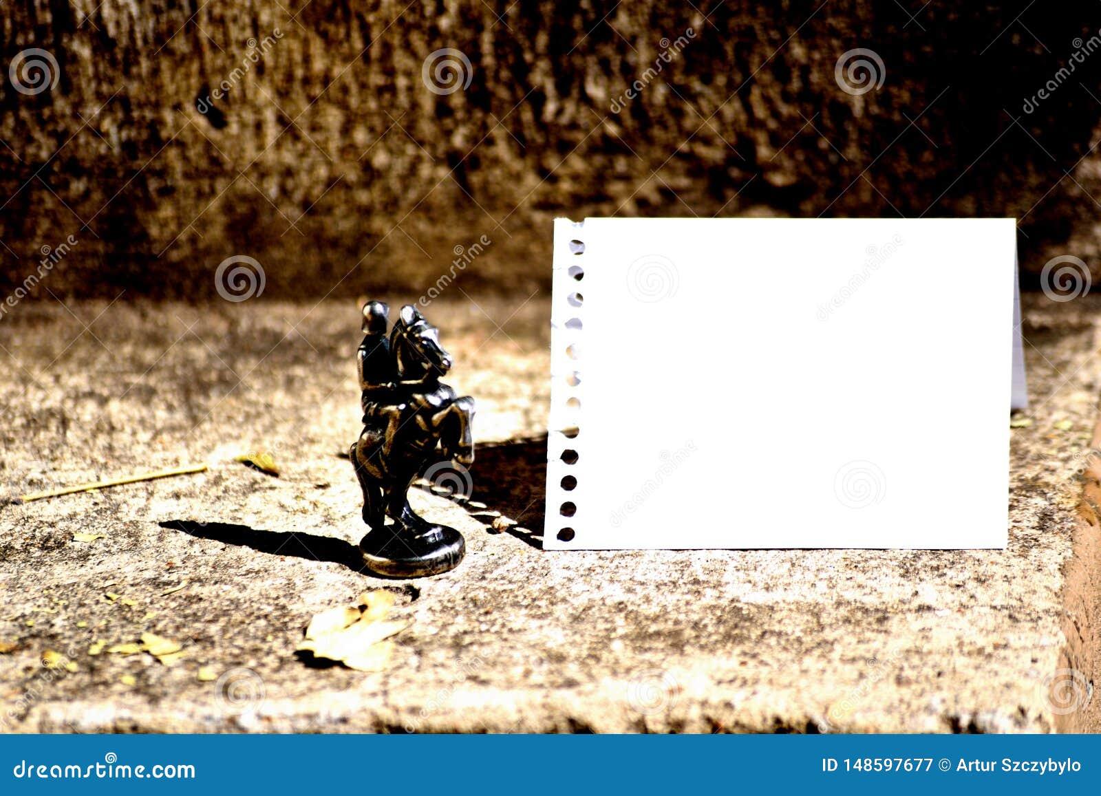 Cavaleiro de bronze Chessman Set da parte de xadrez ao lado e enfrentando a folha vazia do caderno espiral rasgada fora e dobrada