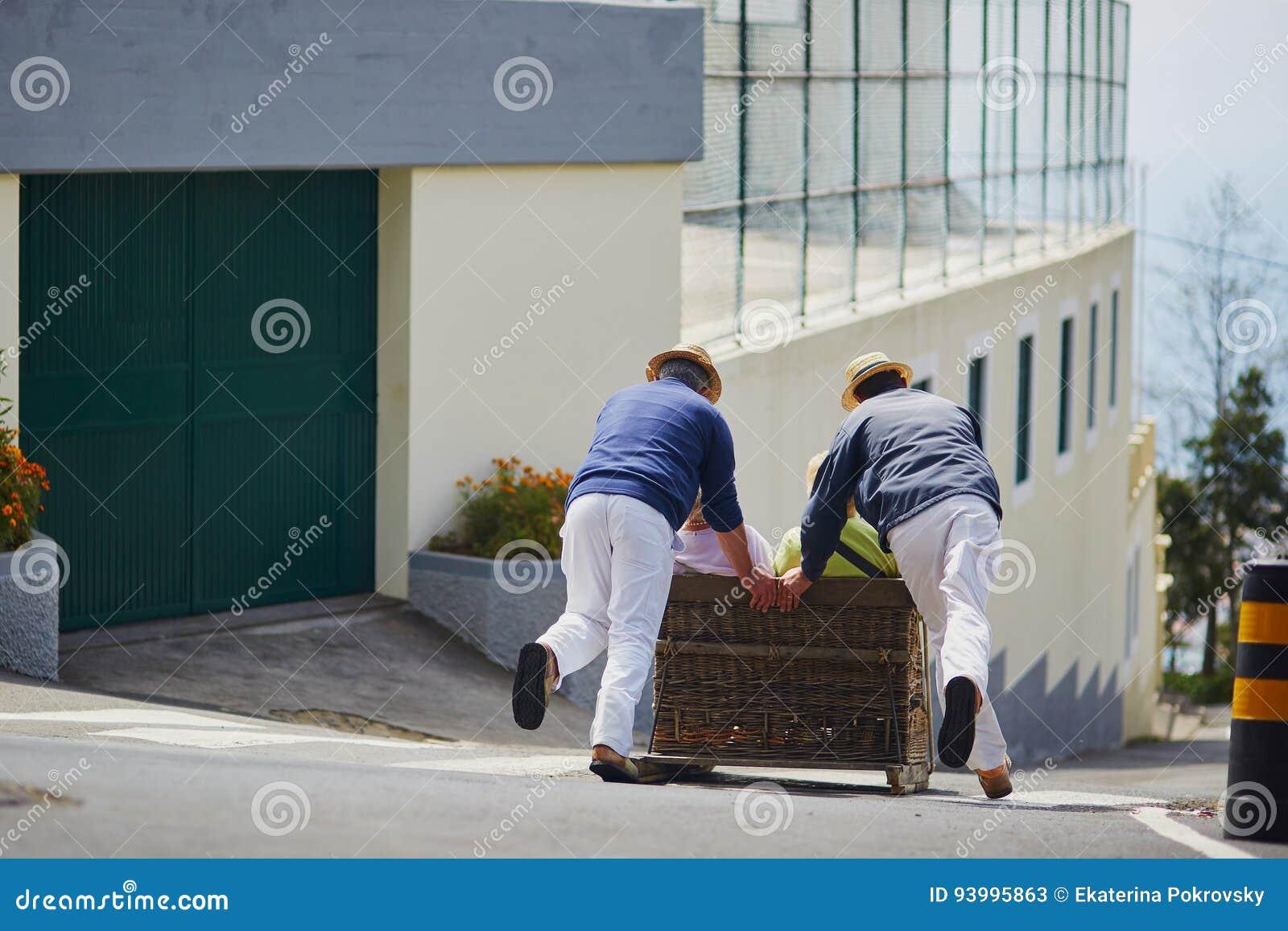 Cavaleiros do Toboggan que movem o pequeno trenó do bastão para baixo nas ruas de Funchal, ilha de Madeira