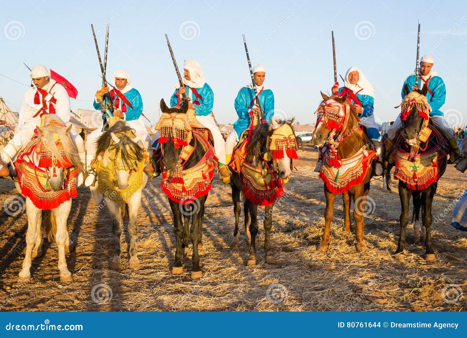 Cavaleiros marroquinos do cavalo durante o festival da fantasia