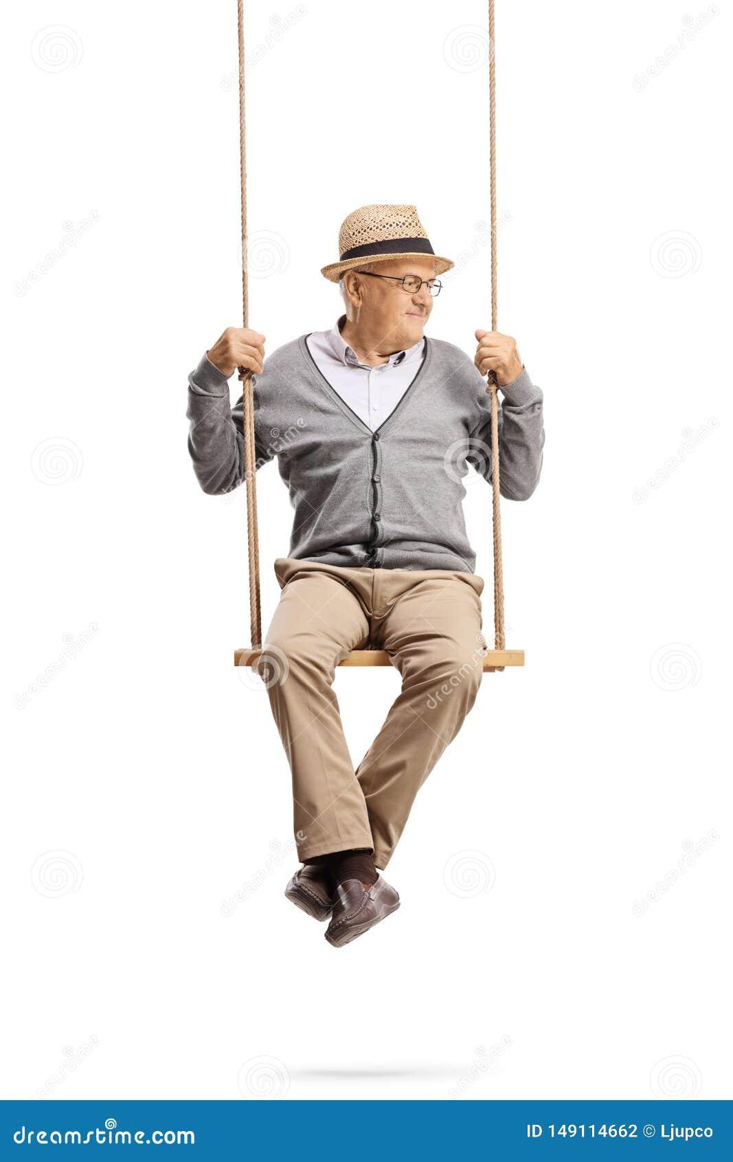 Cavalheiro maduro que senta-se em um balan?o e que olha ao lado