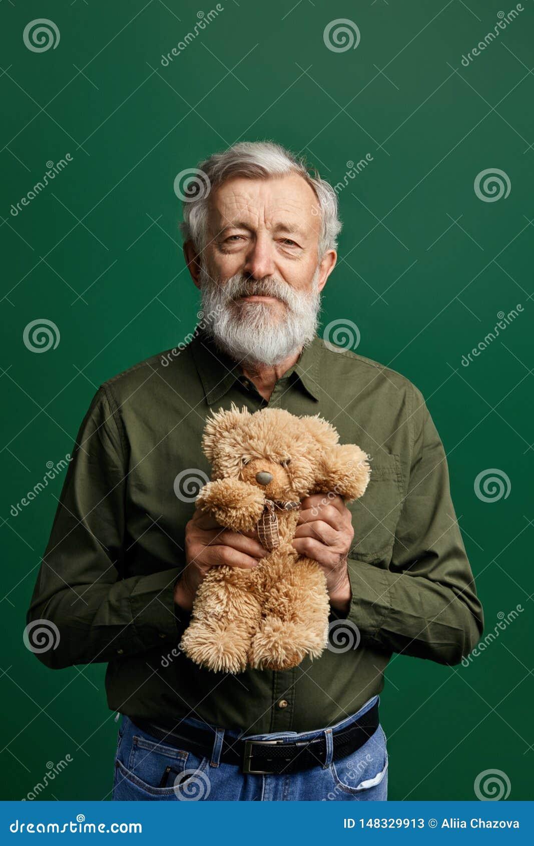 Cavalheiro superior considerável doce que mantém um urso de peluche isolado no fundo verde