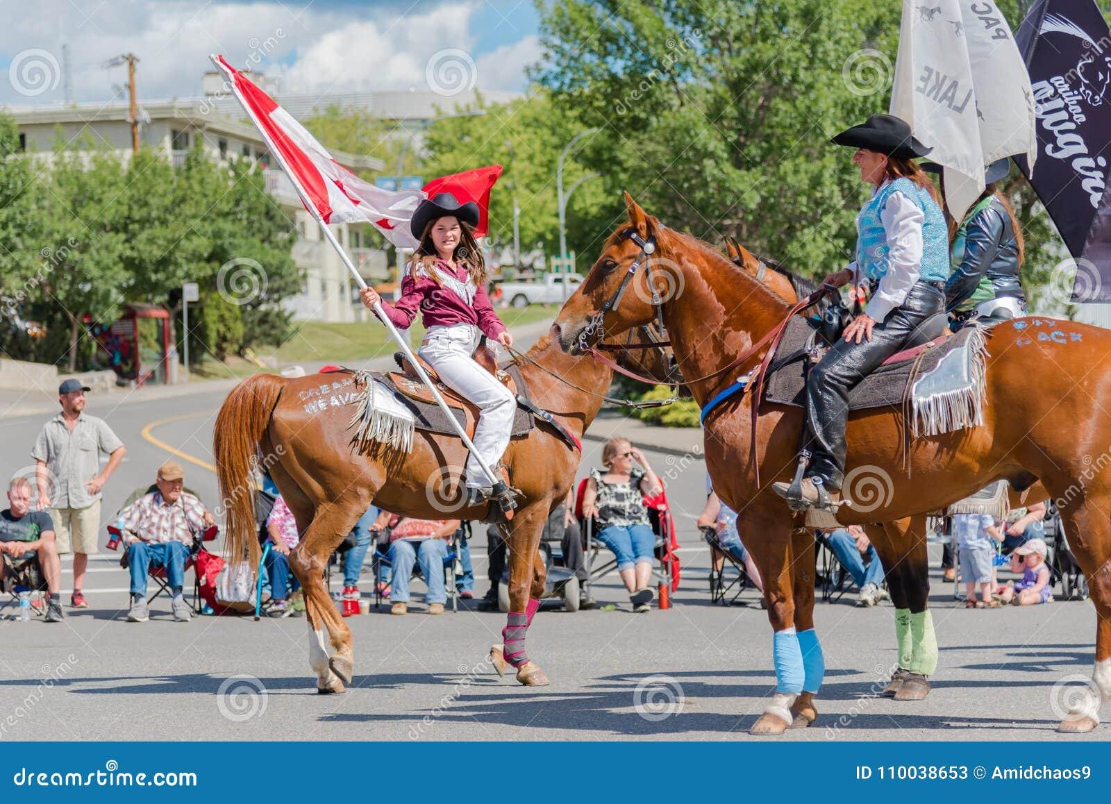 Cavallo da equitazione della ragazza e bandiera canadese d ondeggiamento alla parata