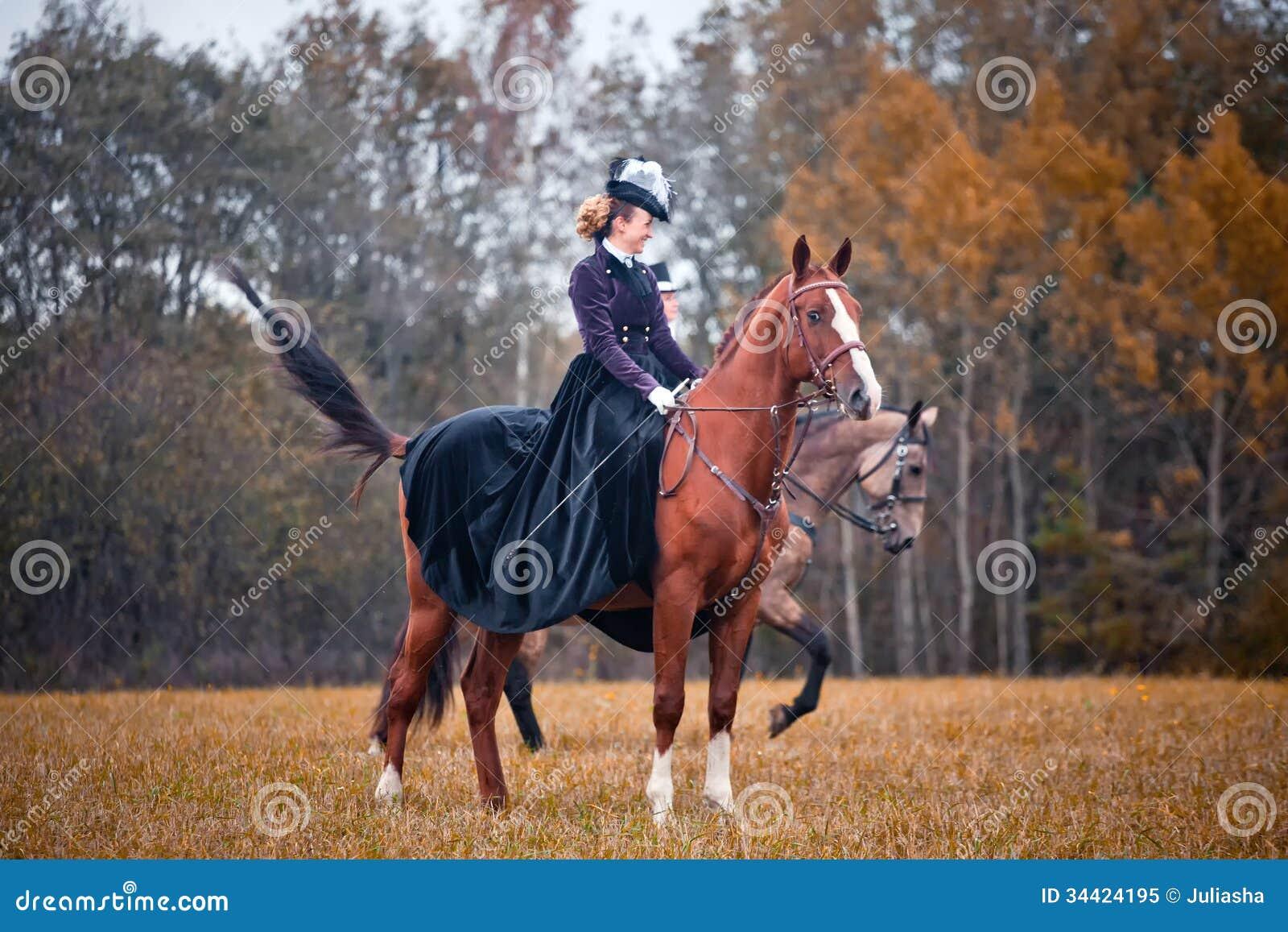 Cavalo-caça com as senhoras no hábito de equitação