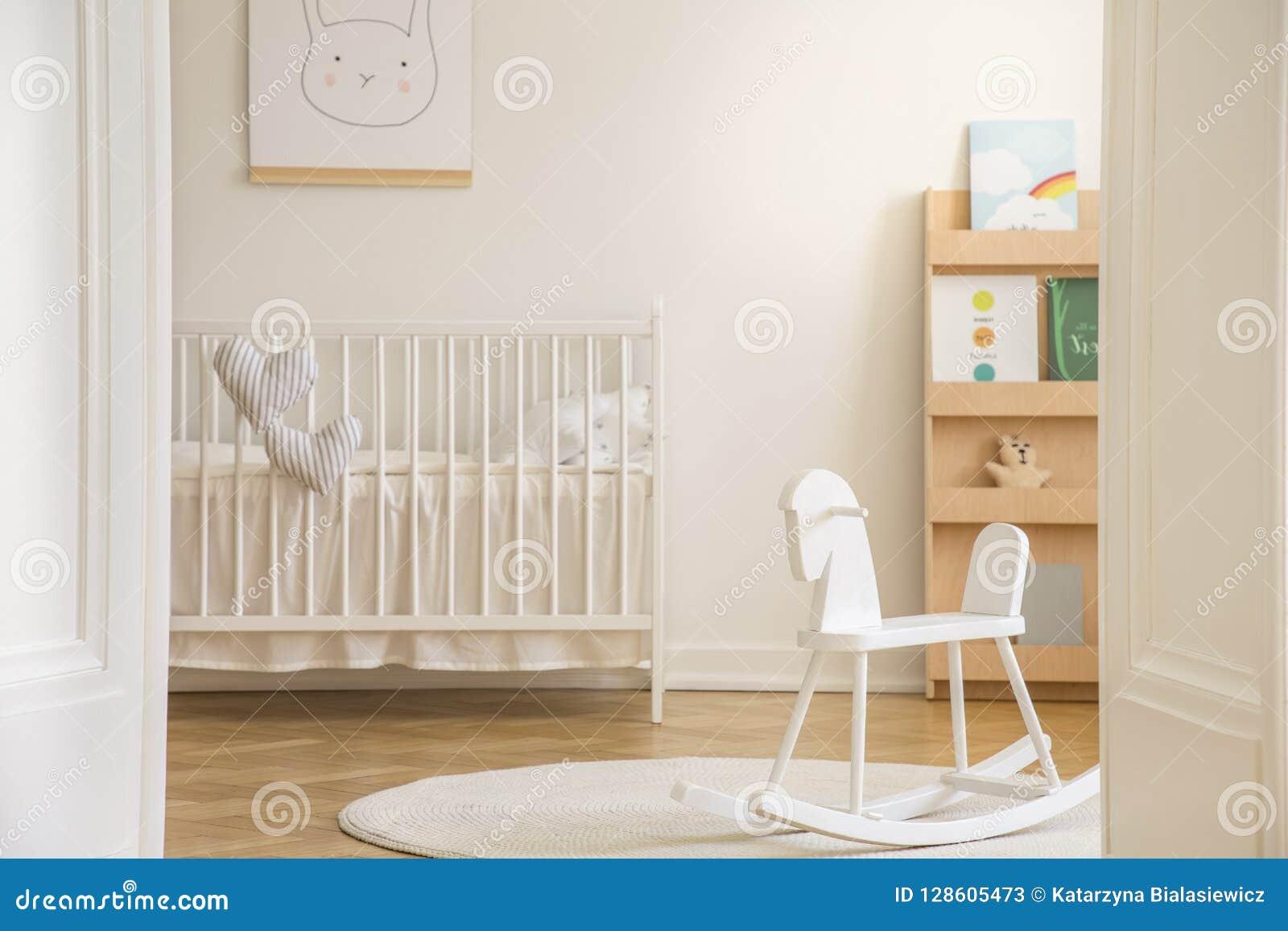 Cavalo de balanço no tapete no interior branco do quarto do ` s da criança com o cartaz do coelho acima do berço