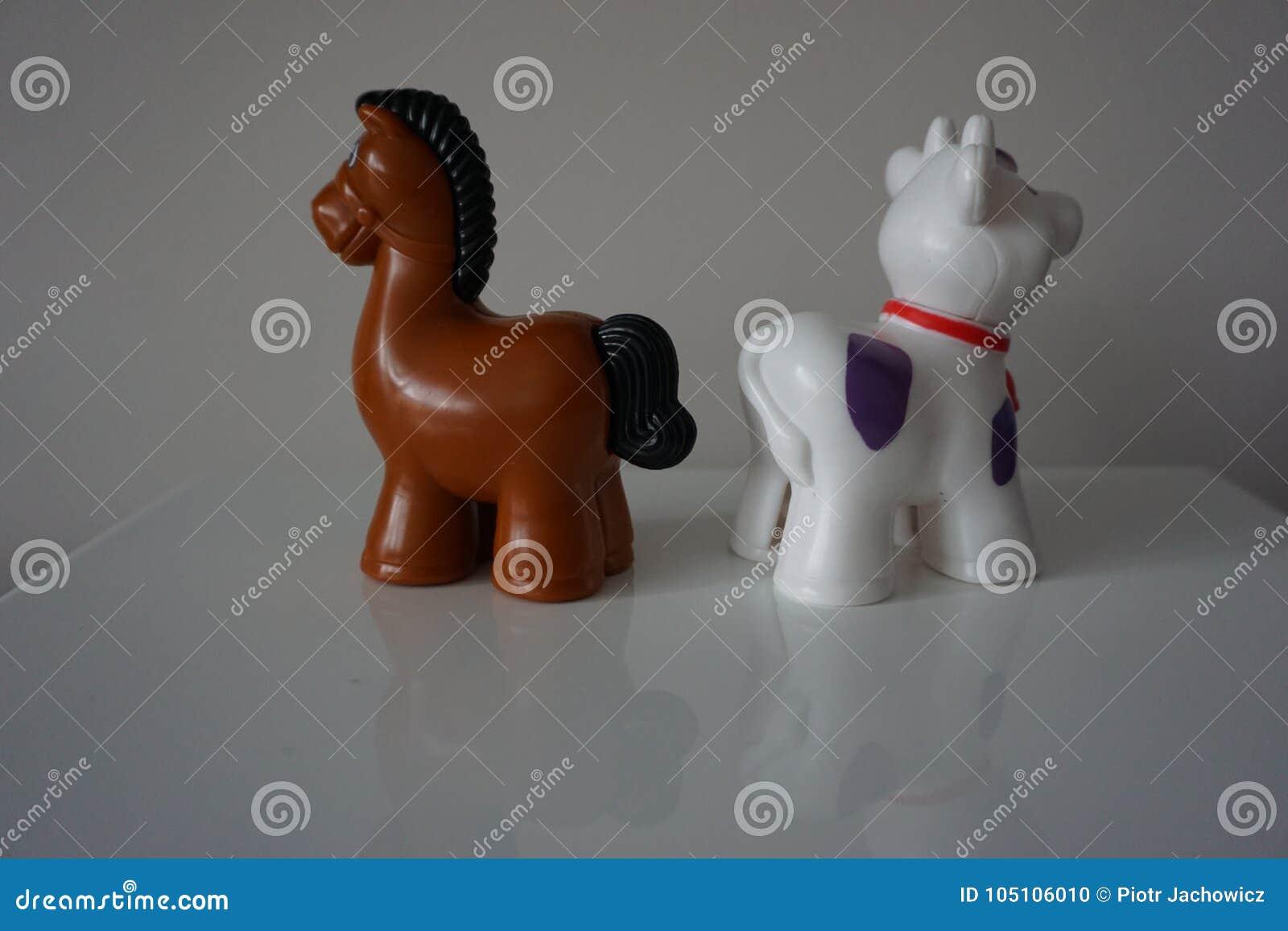 Cavalo de Brown e brinquedos plásticos da vaca branca para a criança