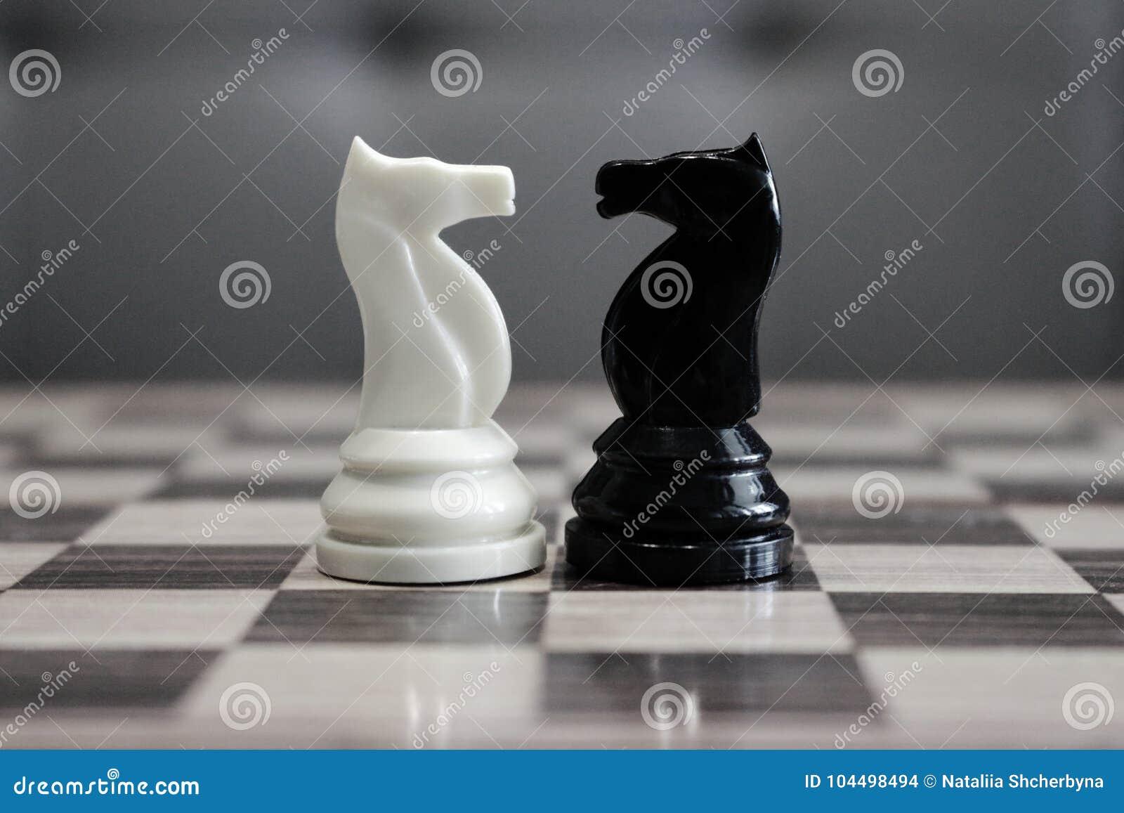 Cavalos preto e branco da xadrez na frente de se como o conceito do desafio e da competição