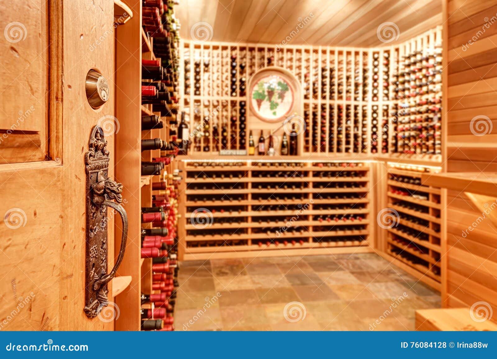 Cave à la maison lumineuse avec les unités de stockage en bois avec des bouteilles