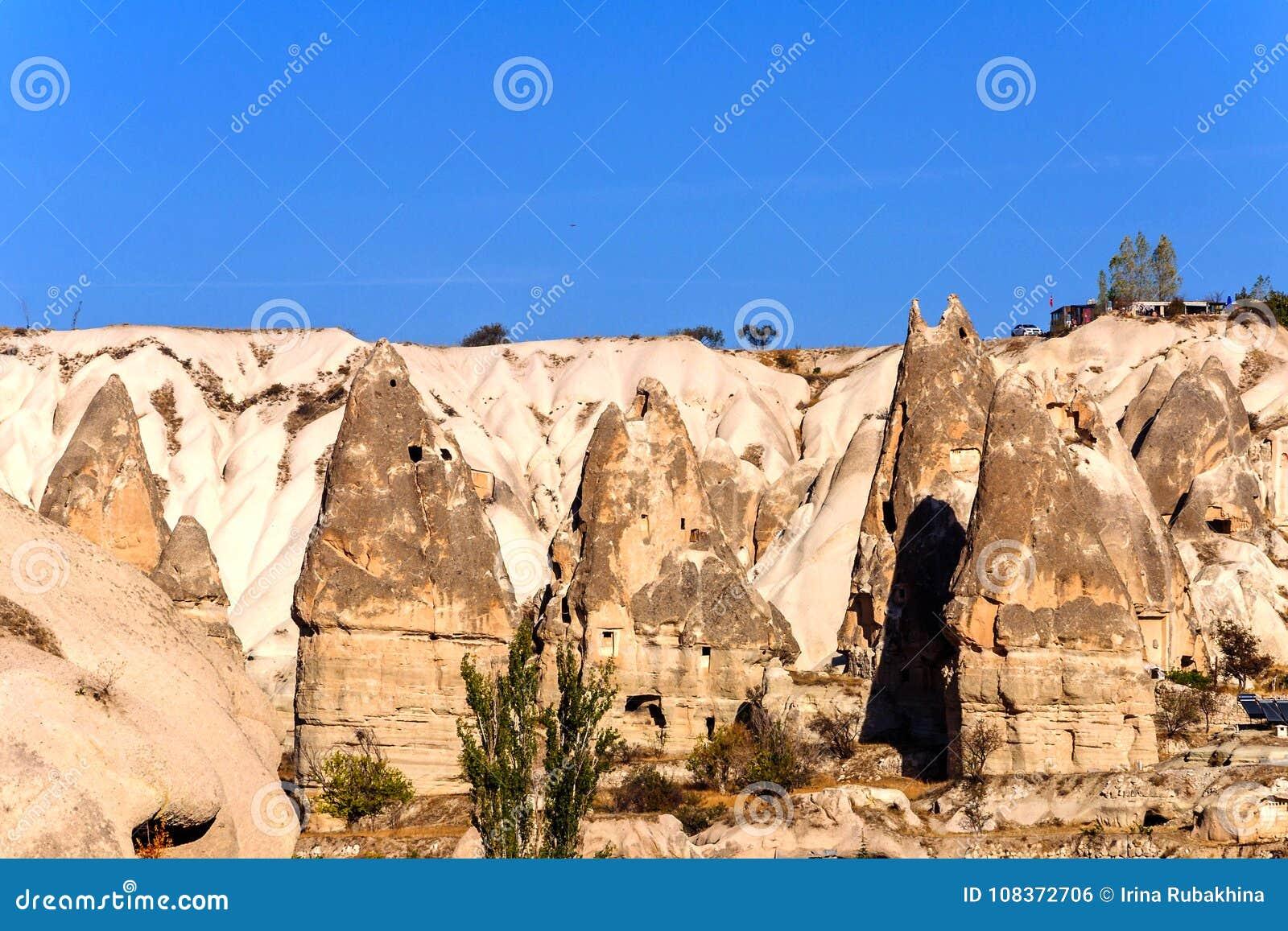 Cave as cidades na formação de rochas vulcânicas, casas de pedra em Goreme, paisagem da montanha cinzelada no tufo Cappadocia, Tu