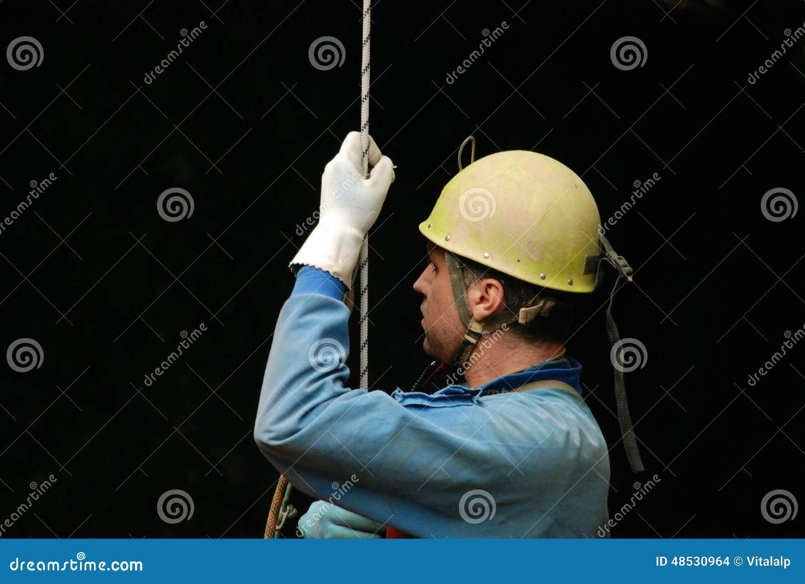 Caver che si cala in corda doppia in una buca