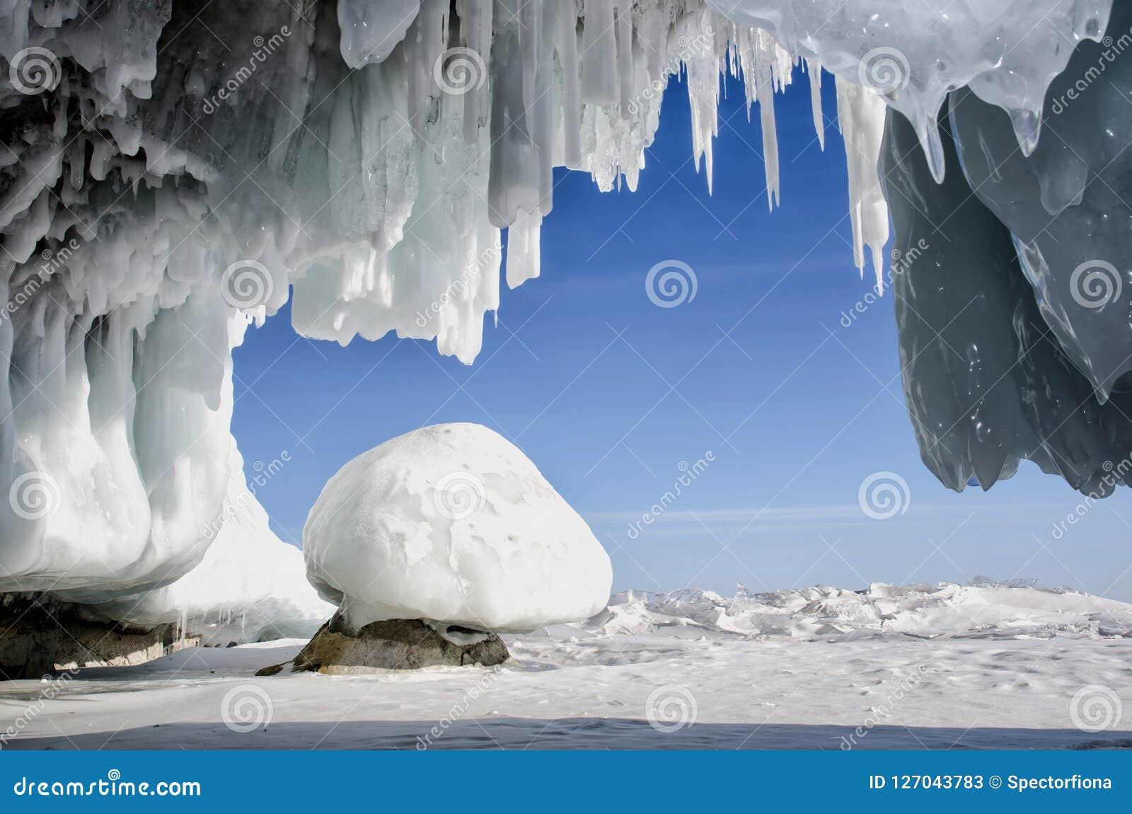 A caverna de gelo branca azul com estalactites do sincelo, o céu azul e a pedra cobriram o gelo