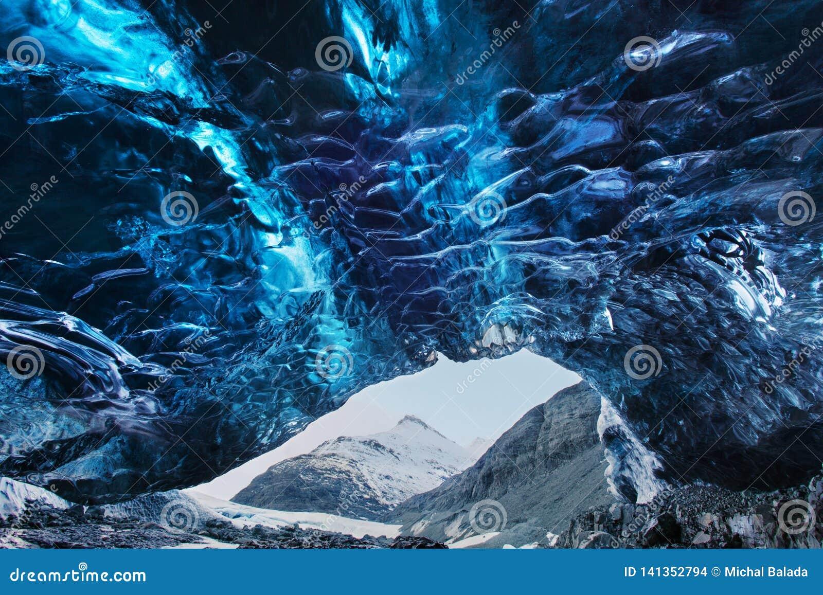 Caverna de gelo de surpresa Caverna de gelo de cristal azul e um rio subterrâneo abaixo da geleira Natureza de surpresa de Skafta