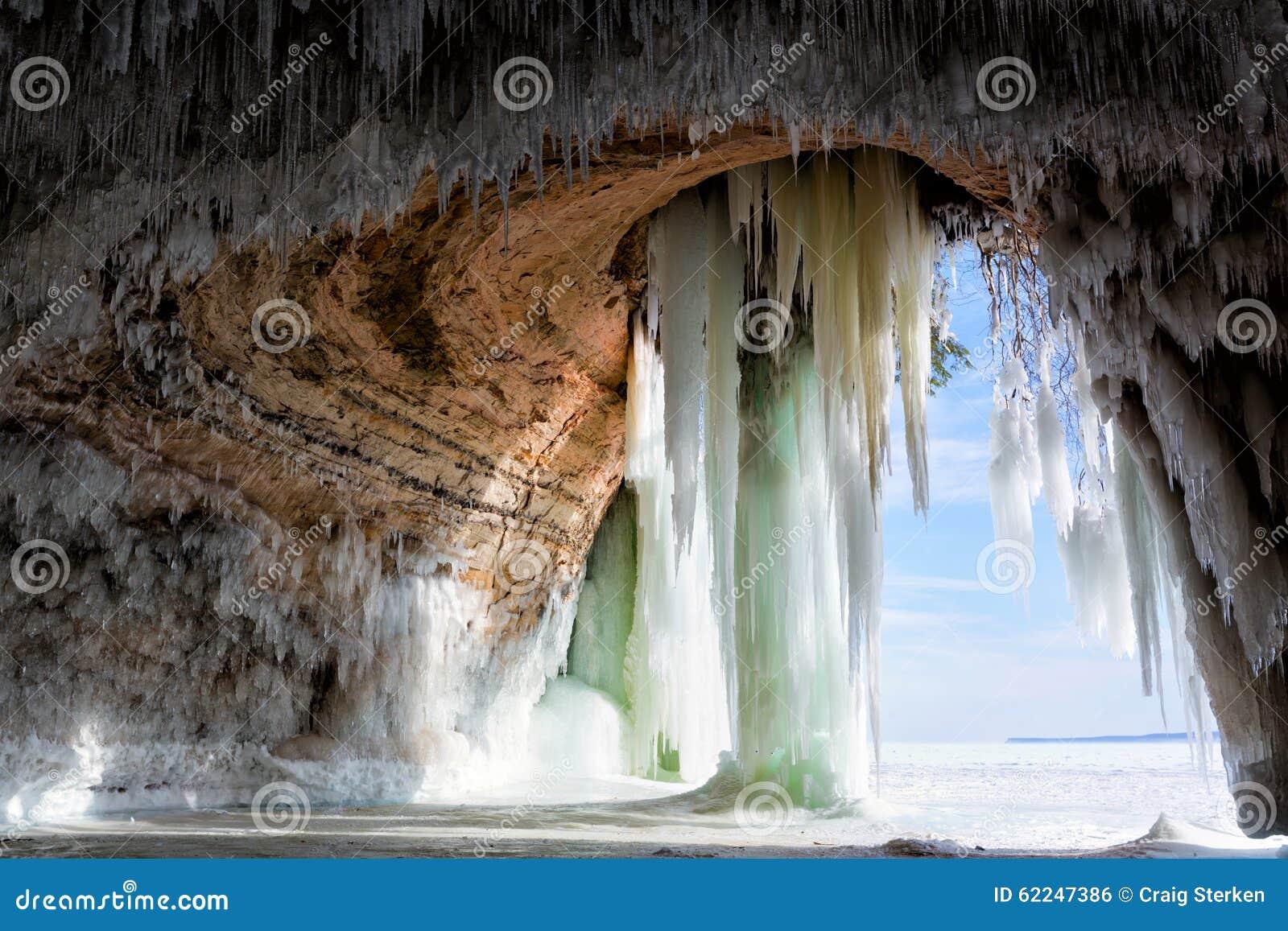 Caverna detrás de las cortinas del hielo en la isla magnífica en el lago Superior