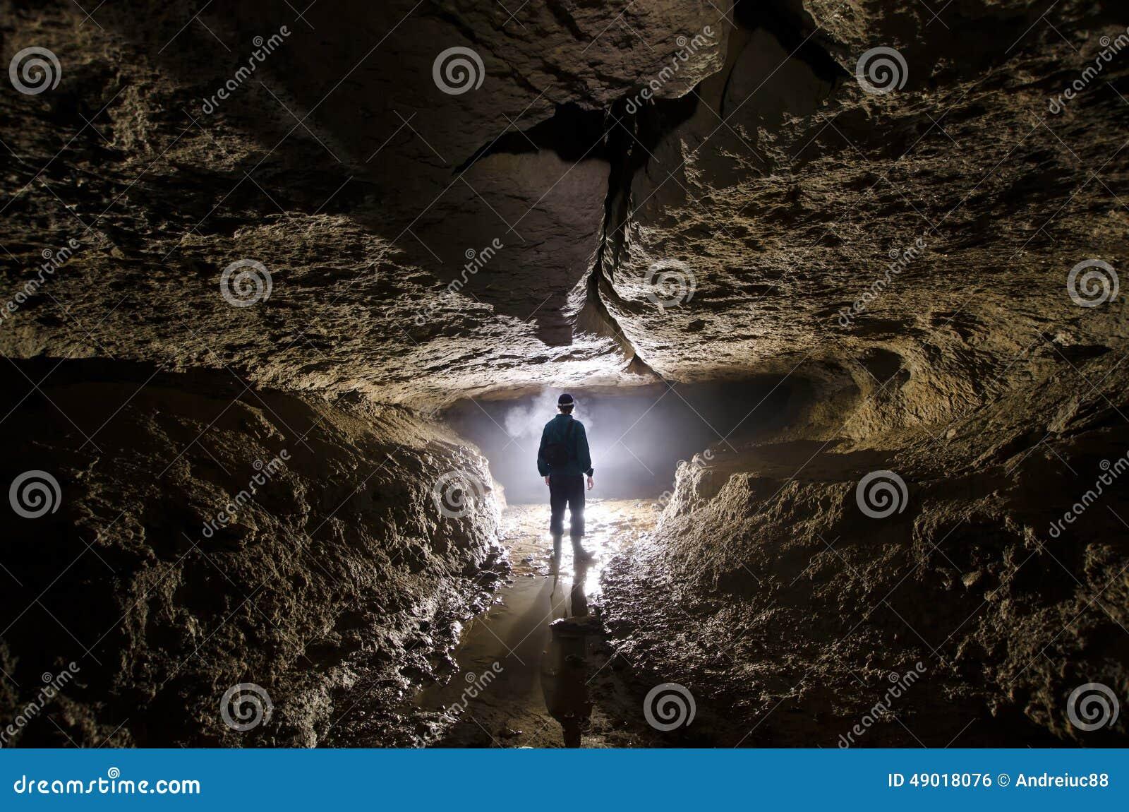 Caverna sotterranea con lo speleologo e la luce dell 39 uomo for Piani di caverna dell uomo