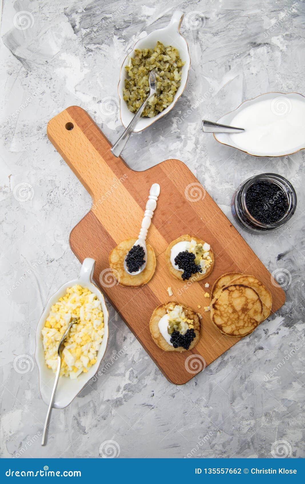 Caviar alemán negro en la cuchara de la perla con los blinis, la crema agria, el condimento del pepino y el huevo tajado