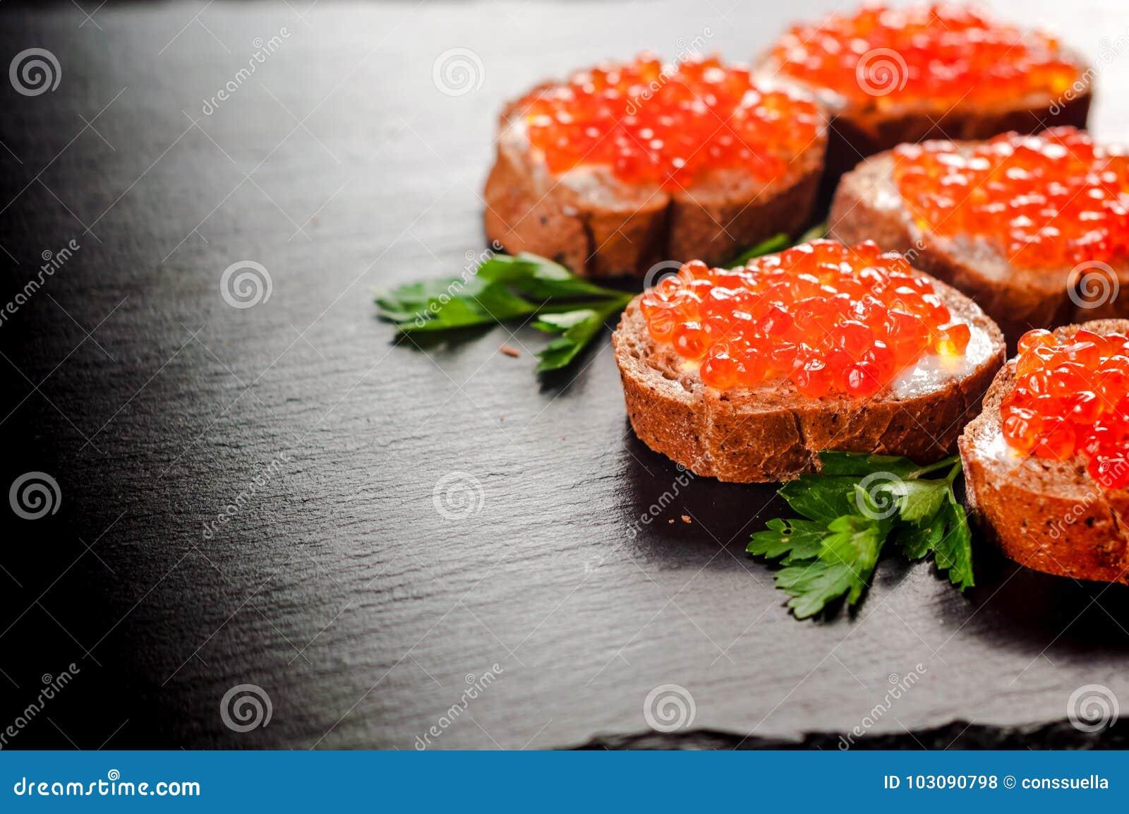 Caviar rojo en el pan negro con mantequilla Alimento sano Aperitivo de los pescados Fondo oscuro