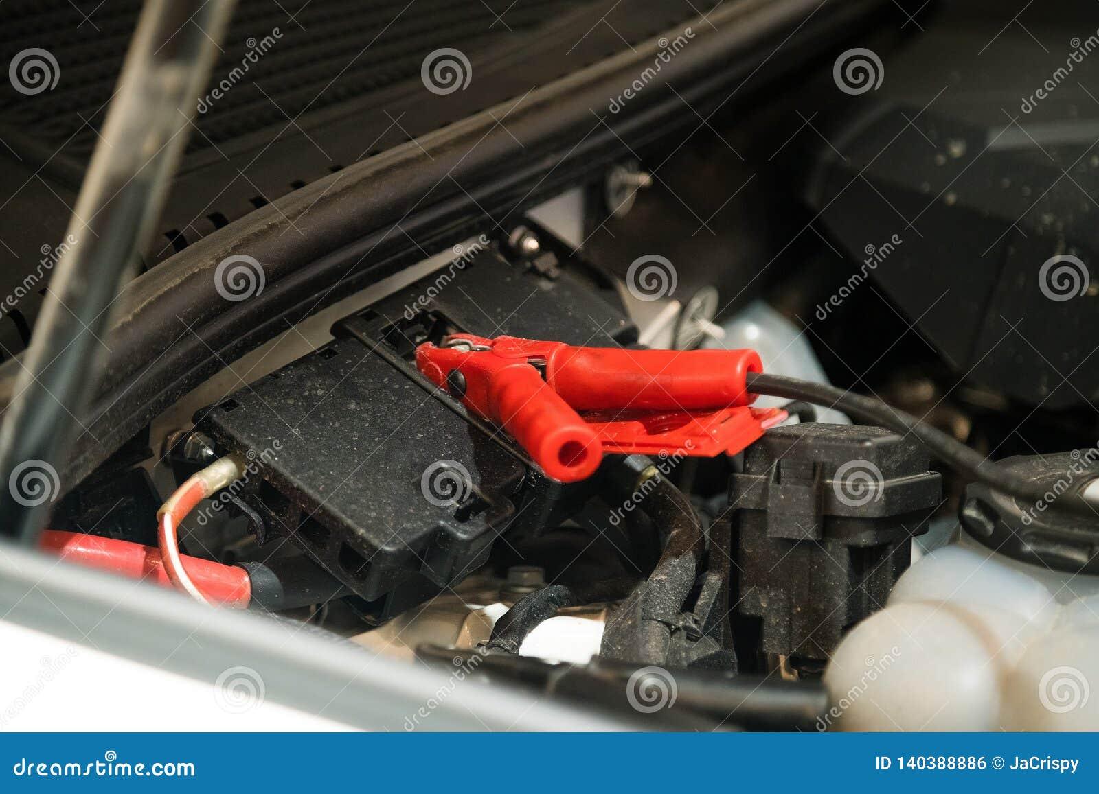 Cavo di saltatore allegato sotto il cappuccio dell automobile per contribuire ad avviare il motore dell automobile Gruppo di lavo