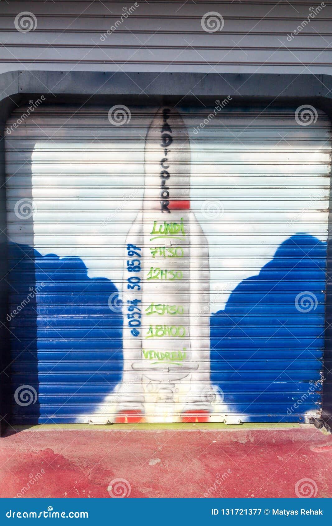 CAYENNEPFEFFER, FRANZÖSISCH-GUAYANA - 1. AUGUST 2015: Rocket Ariane 5 malte auf einem Eingang zur Garage in der Mitte von Cayenne