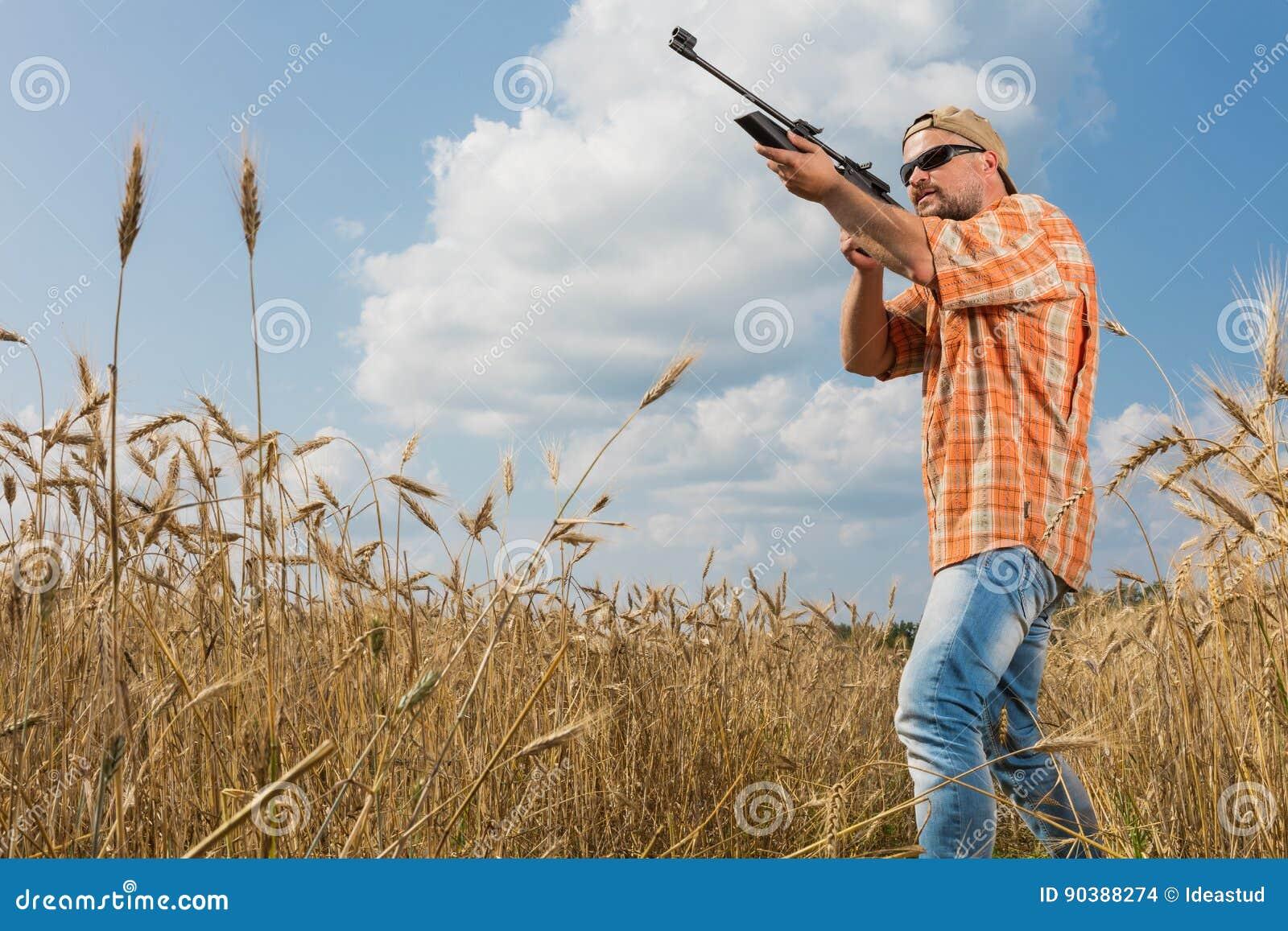 Cazador en el casquillo y las gafas de sol que apuntan un arma al campo