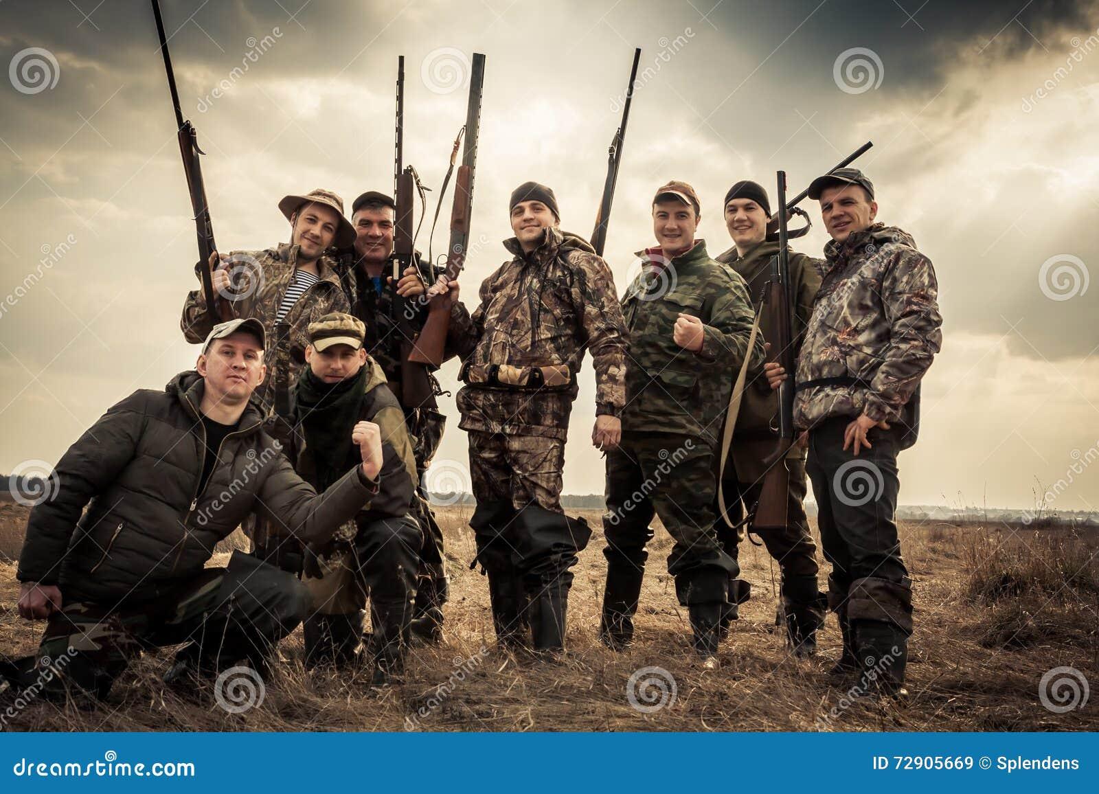 Cazadores que se unen contra el cielo de la salida del sol en campo rural durante temporada de caza Concepto para el trabajo en e