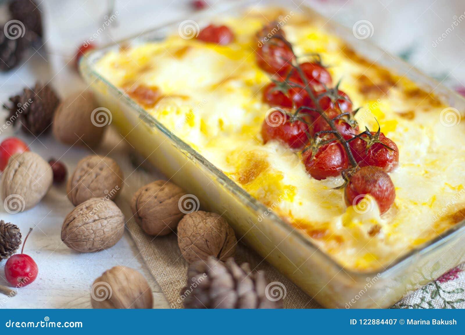 Cazuela con los tomates y el queso para un almuerzo delicioso Visión superior