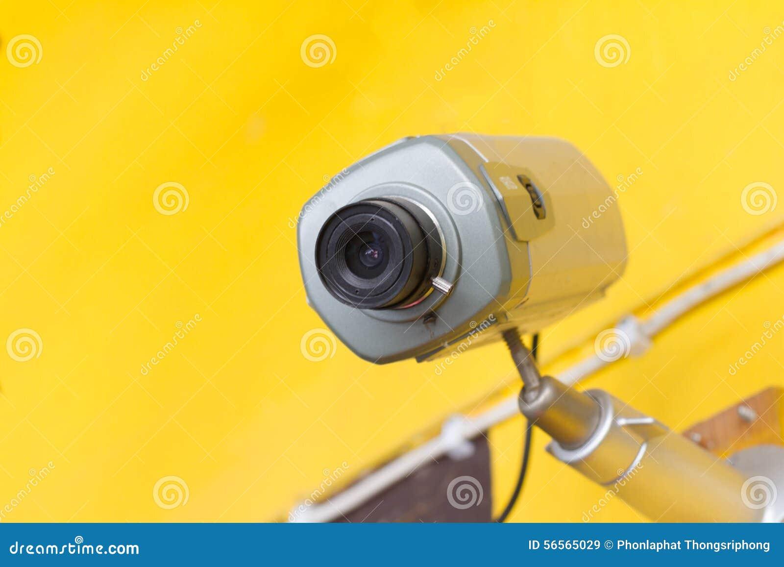 Download CCTV σε έναν κίτρινο τοίχο στοκ εικόνα. εικόνα από εξασφαλίστε - 56565029