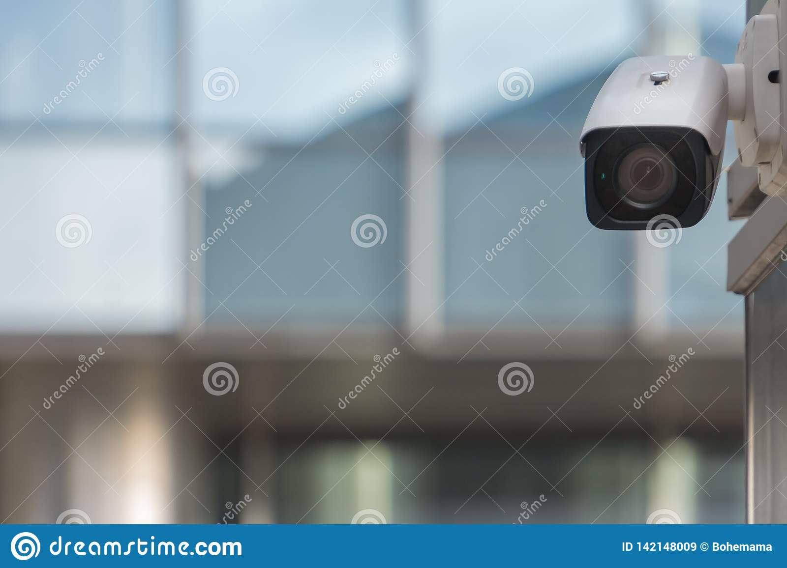 CCTV security camera on modern building wall in city