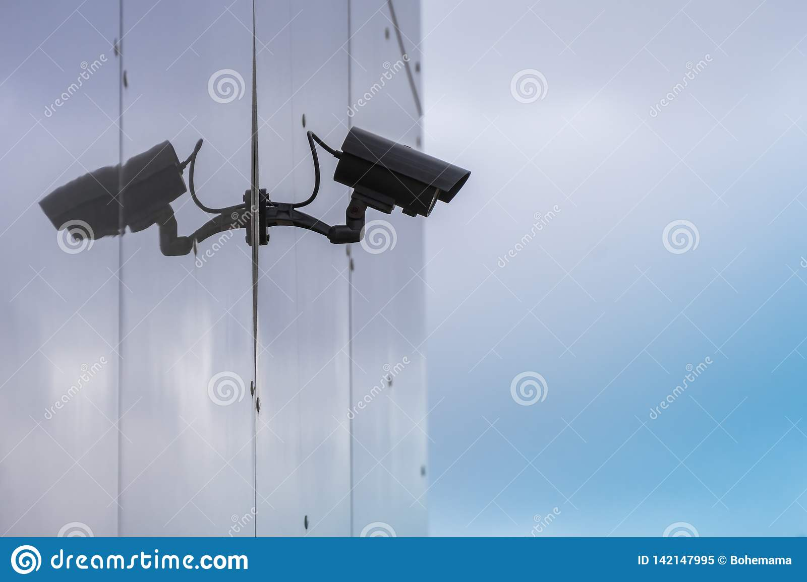 CCTV security camera on modern glass building wall with reflection