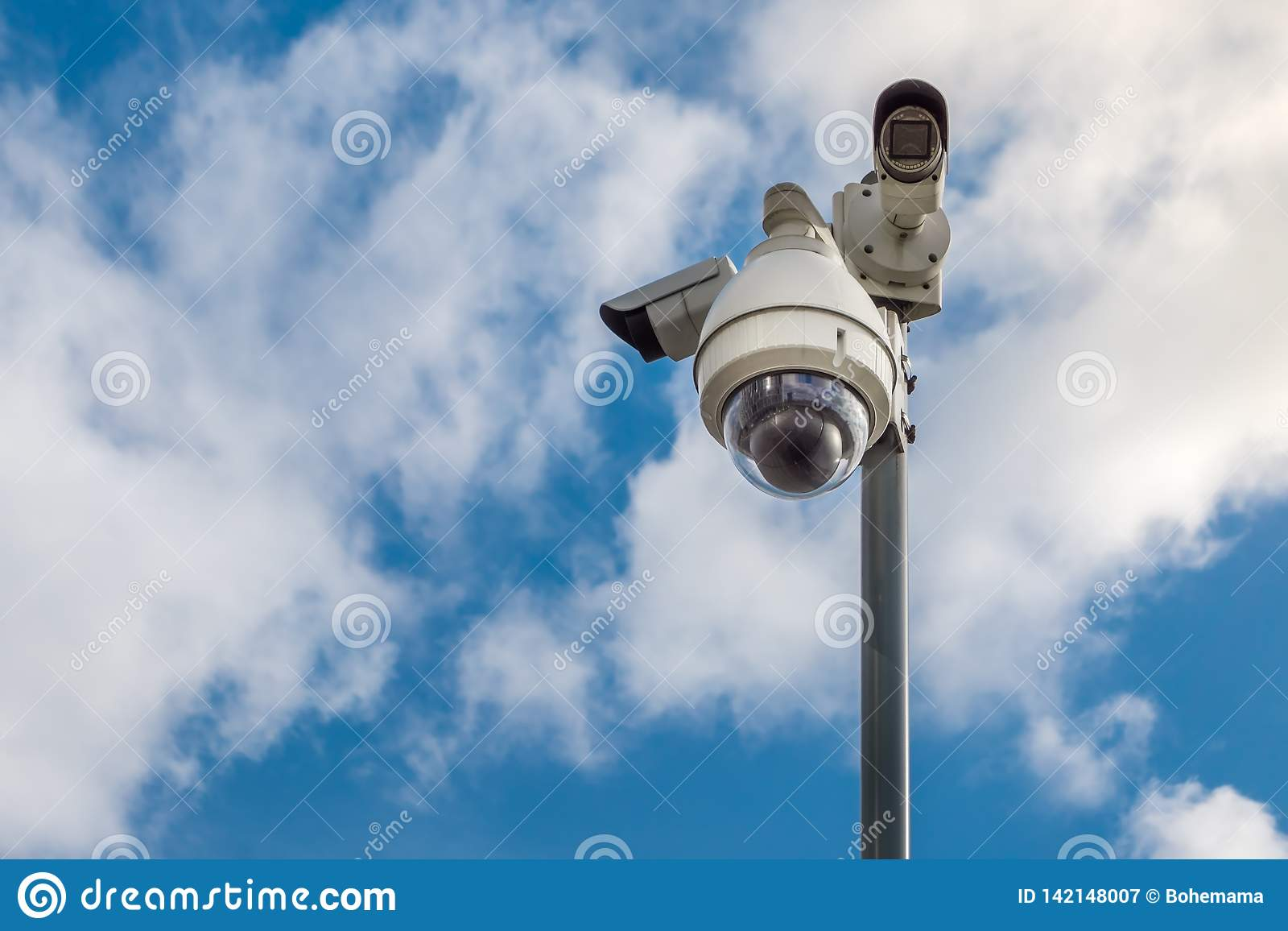 CCTV security cameras on pole on blue sky with white clouds background