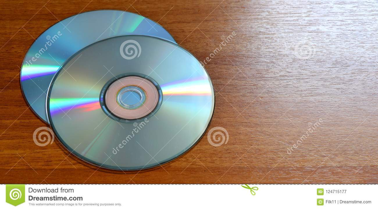 Compact discs on a wooden background. CD on board made of wood