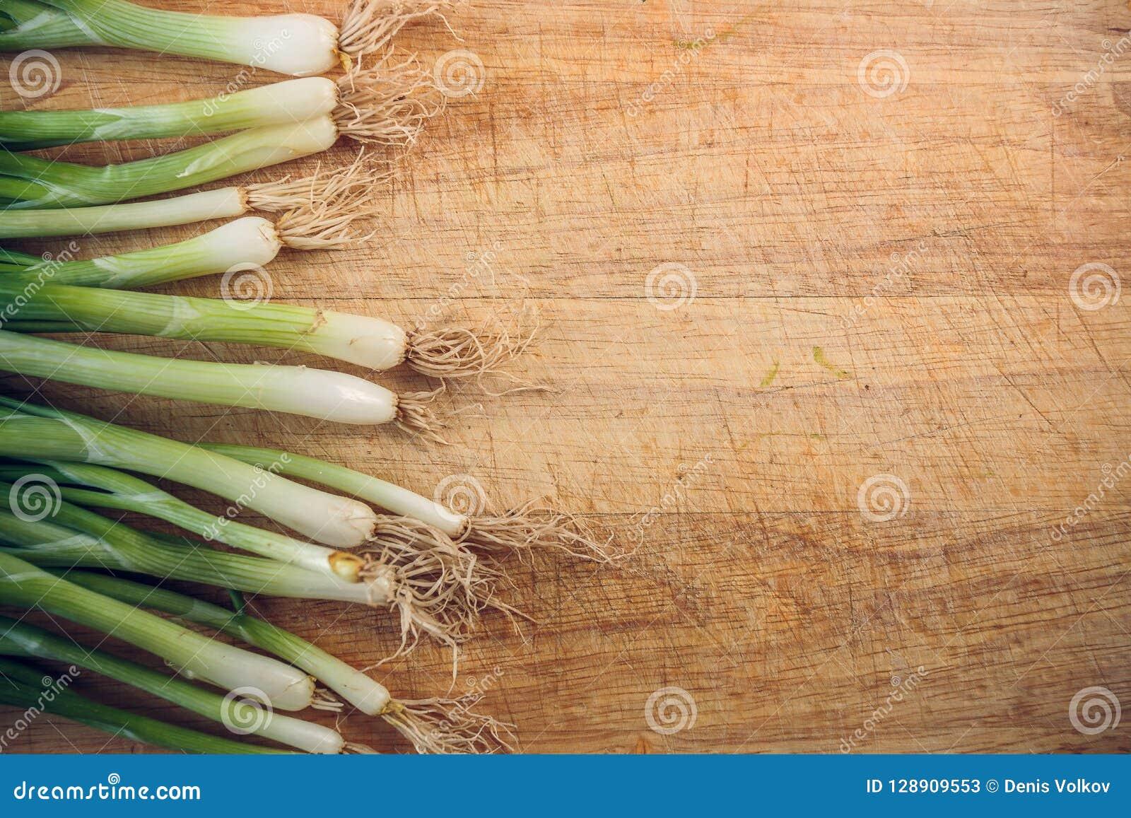 Cebolas verdes frescas que encontram-se em uma placa de desbastamento de madeira A vista da parte superior