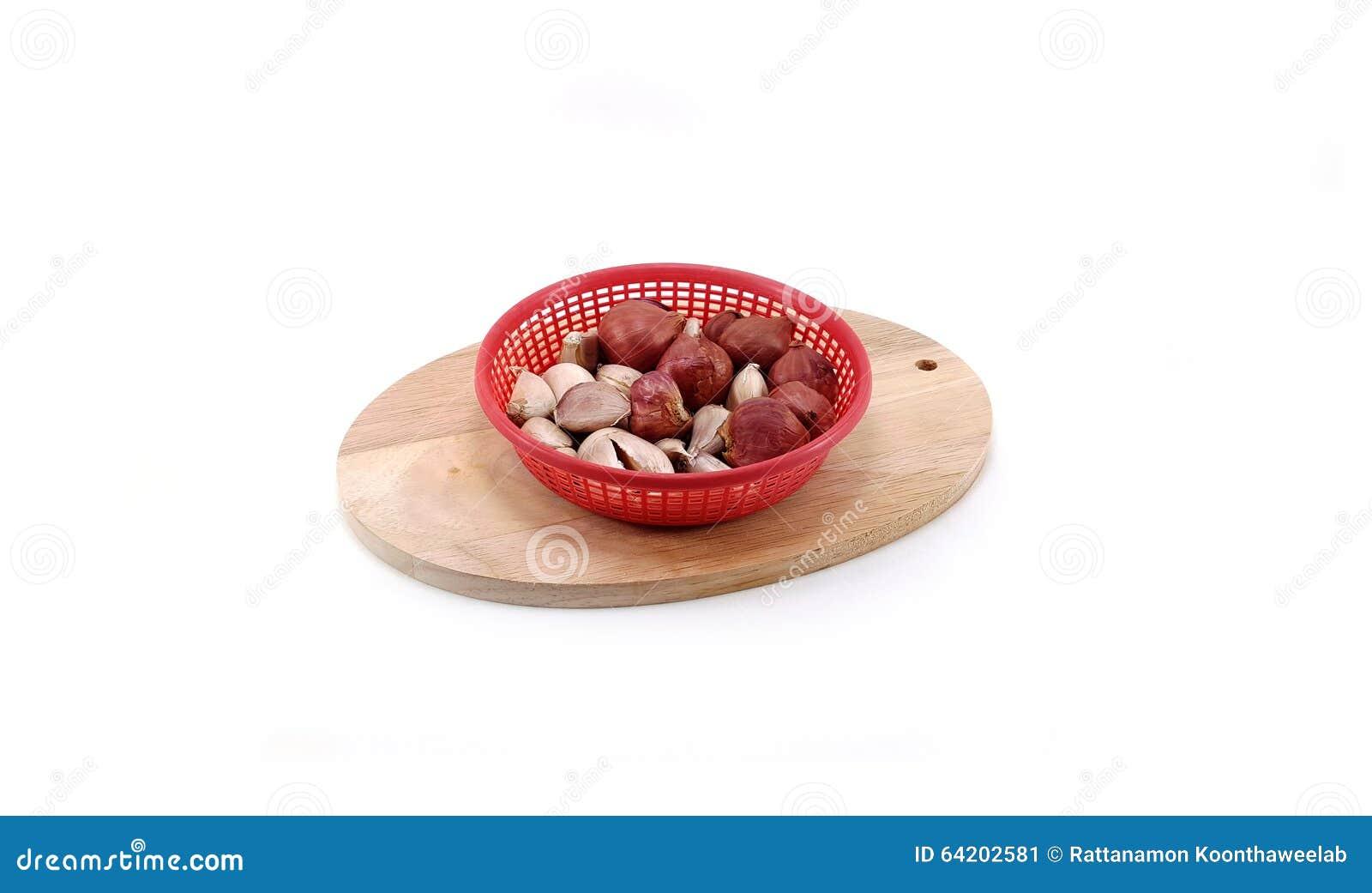 Cebolla roja y ajo en tabla de cortar de madera