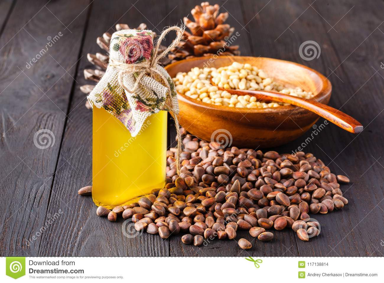 Cedar cone with nuts and a glass bottle with oil on a wooden background. The source of natural vitamins and minerals. Used in folk