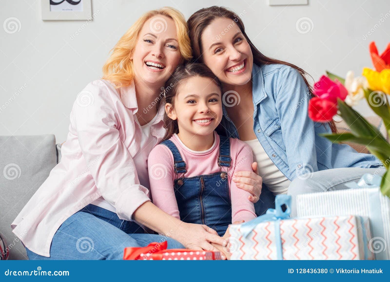 Celebração da mãe e da filha da avó junto em casa que senta-se abraçando o sorriso alegre