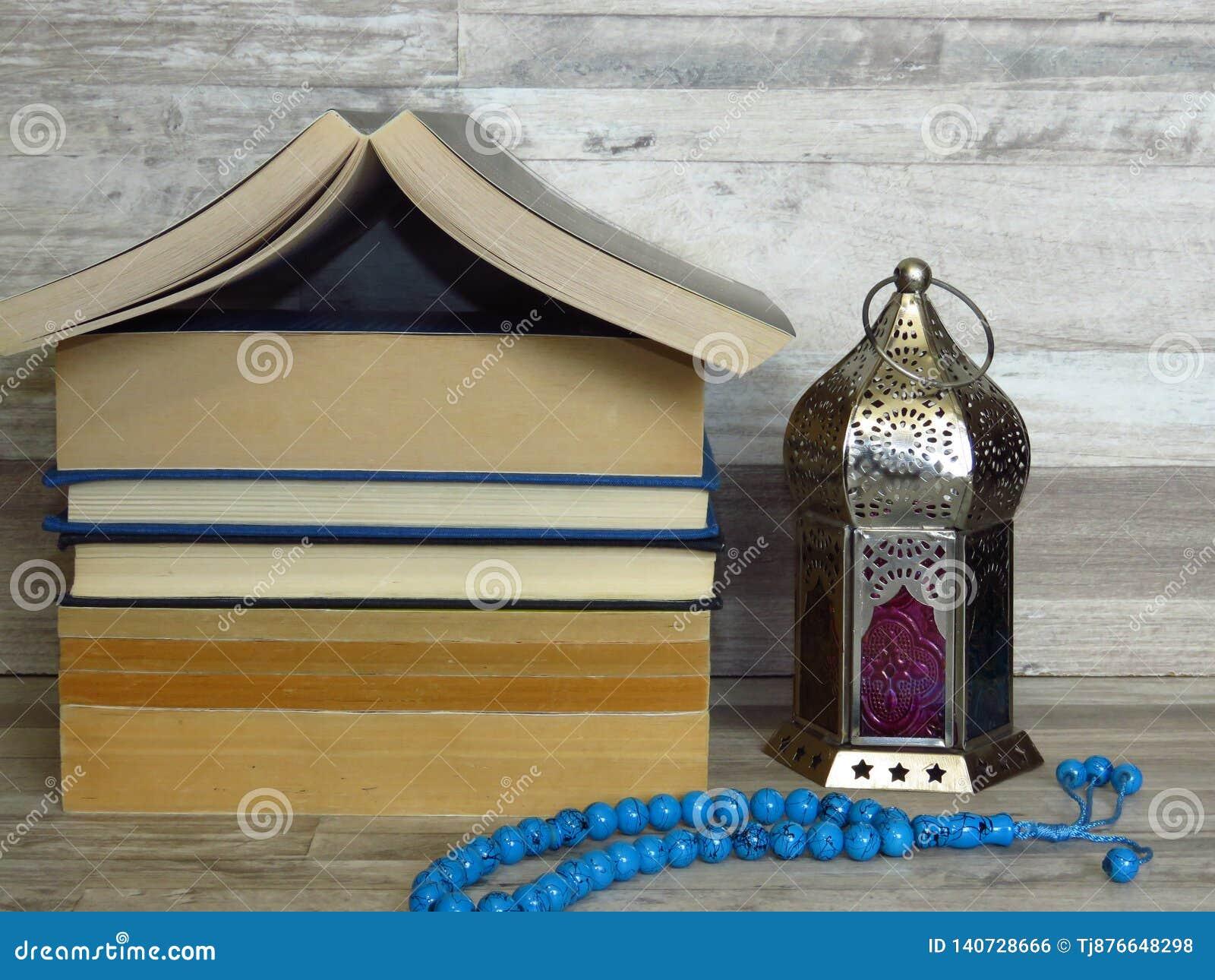 Celebração do tempo de Ramadan Ramazan Uma pilha da casa deu forma a livros velhos, lanterna de prata da ramadã, chaplet azul de