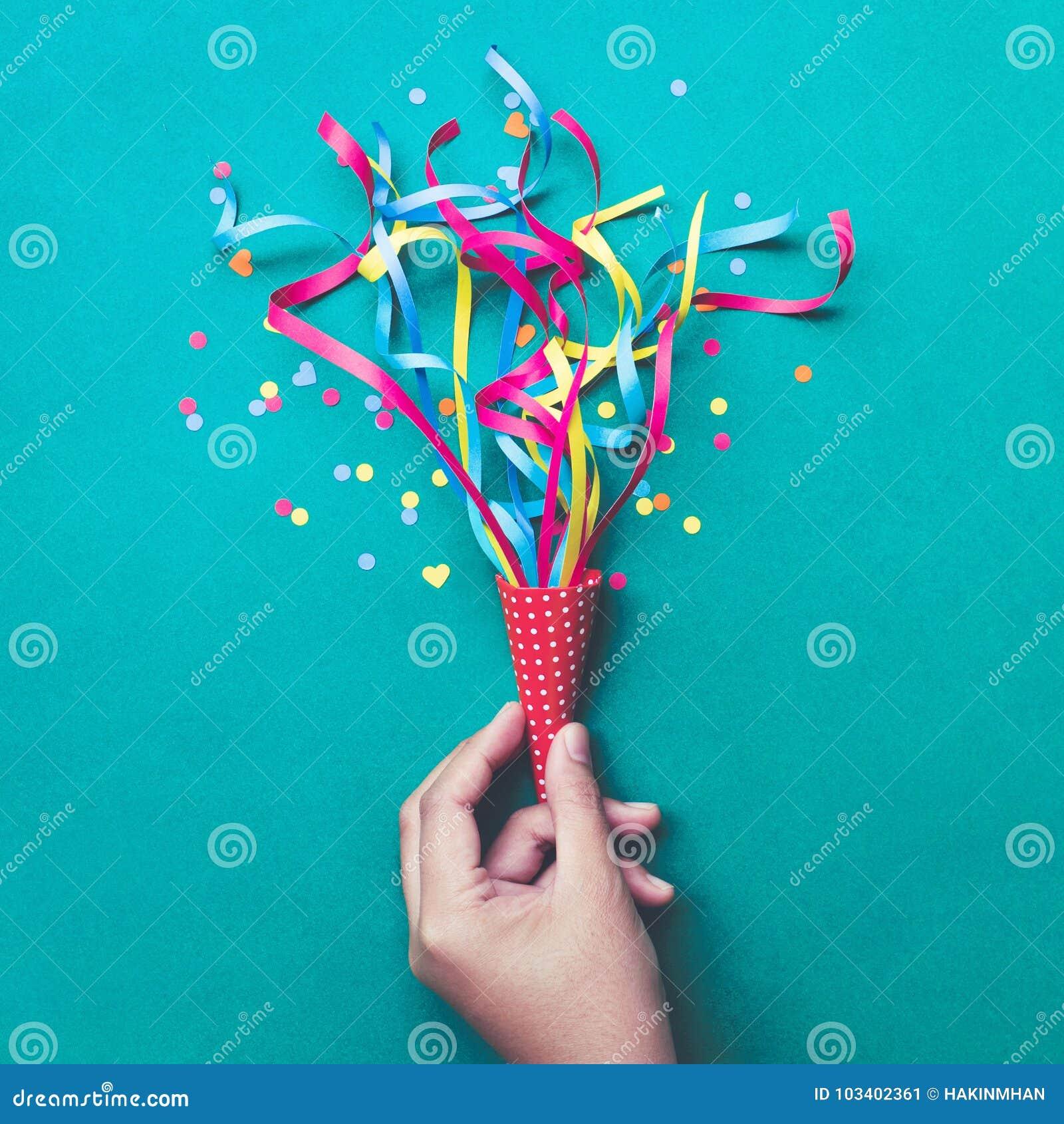 Celebração, ideias dos conceitos dos fundos do partido com a mão que guarda confetes coloridos, flâmulas