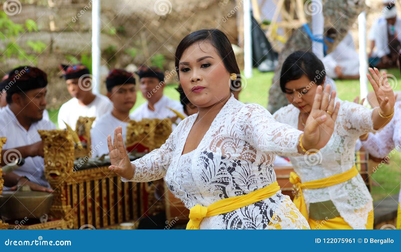 Celebración hindú en Bali Indonesia, ceremonia religiosa con los colores amarillos y blancos, baile de la mujer