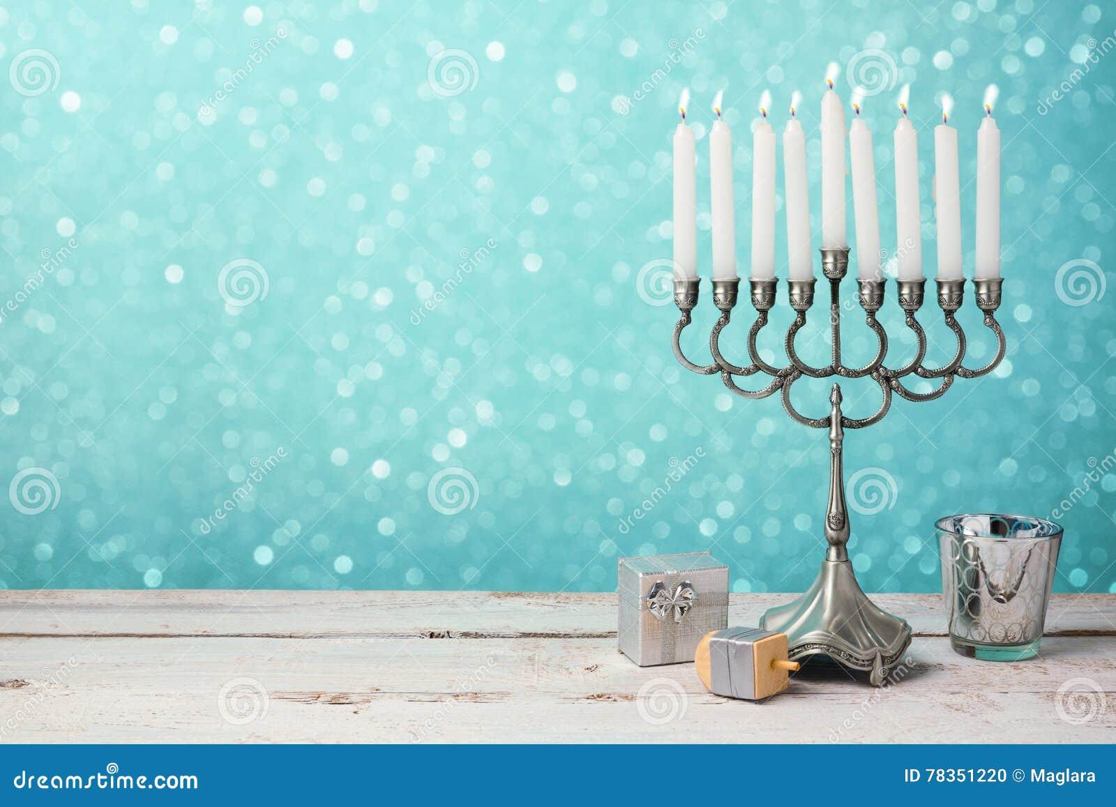 Celebración judía de Jánuca del día de fiesta con el menorah, el dreidel y los regalos en la tabla de madera