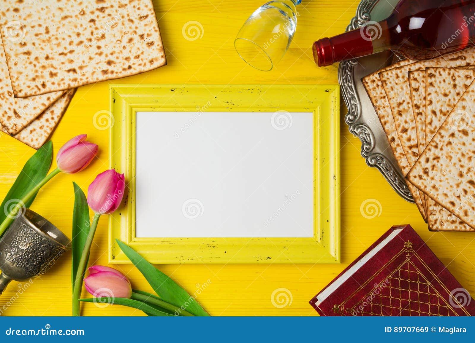 Celebración judía de Pesah de la pascua judía del día de fiesta con el marco de la foto, el matzoh y la botella de vino en fondo