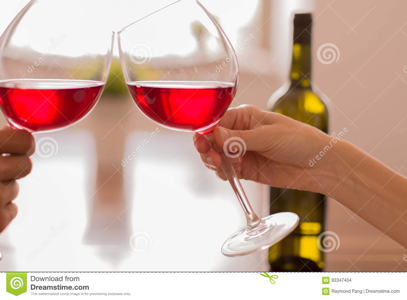 Celebrating by clinking glasses of red wine