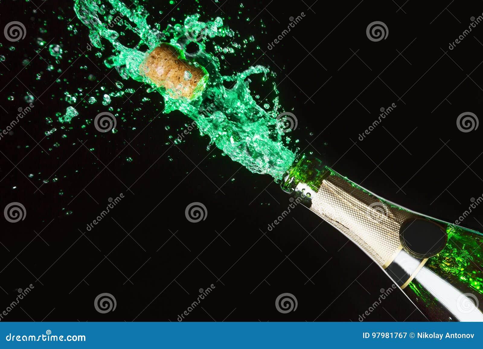 Celebration alcohol theme with explosion of splashing green absinth on black background.