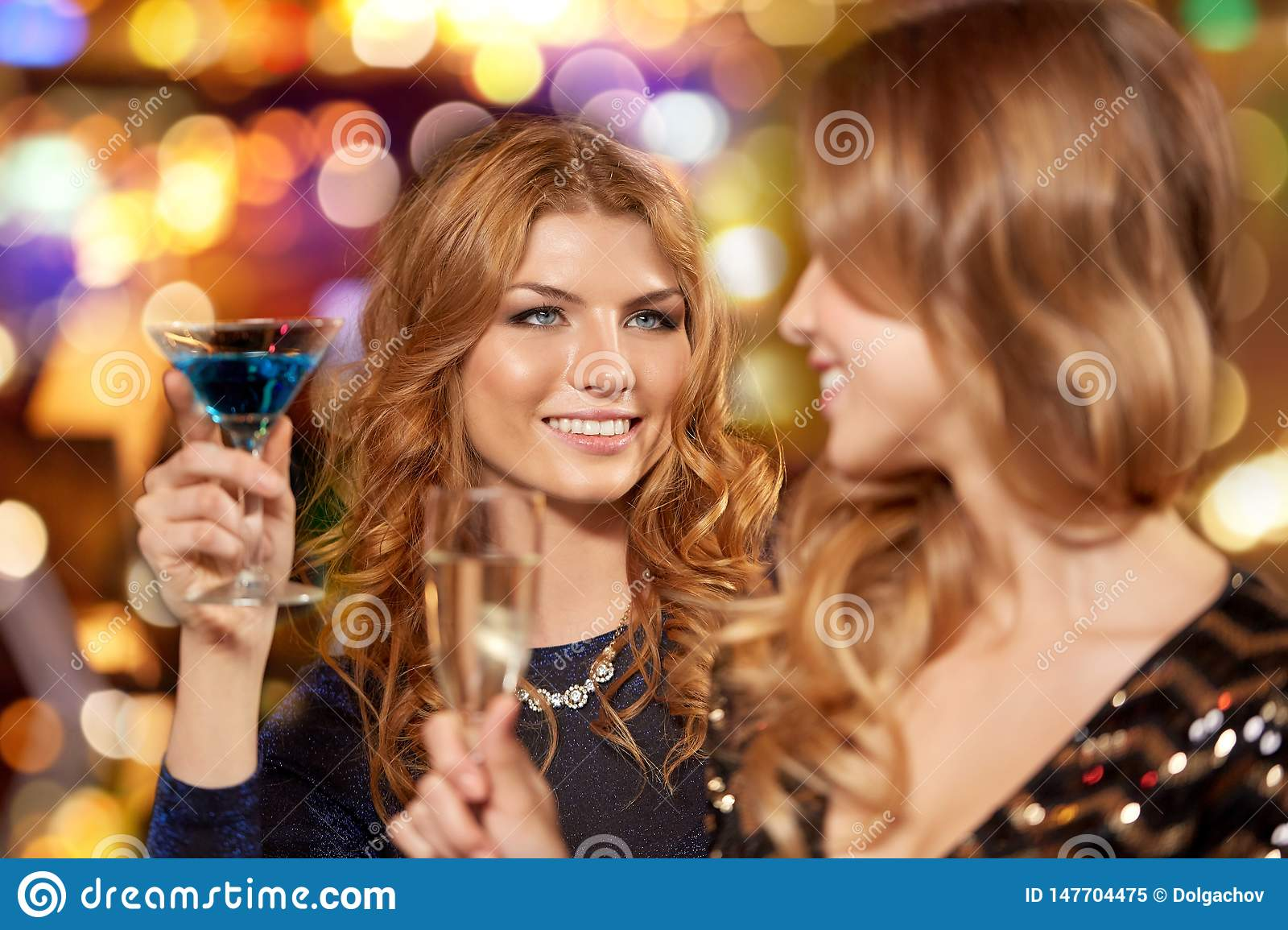 Happy women drinks in glasses at night club