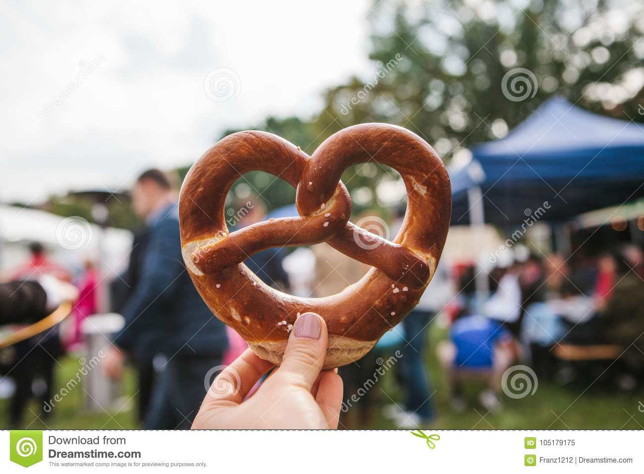 Celebration of the famous German beer festival Oktoberfest. The person holds in his hand a traditional pretzel called