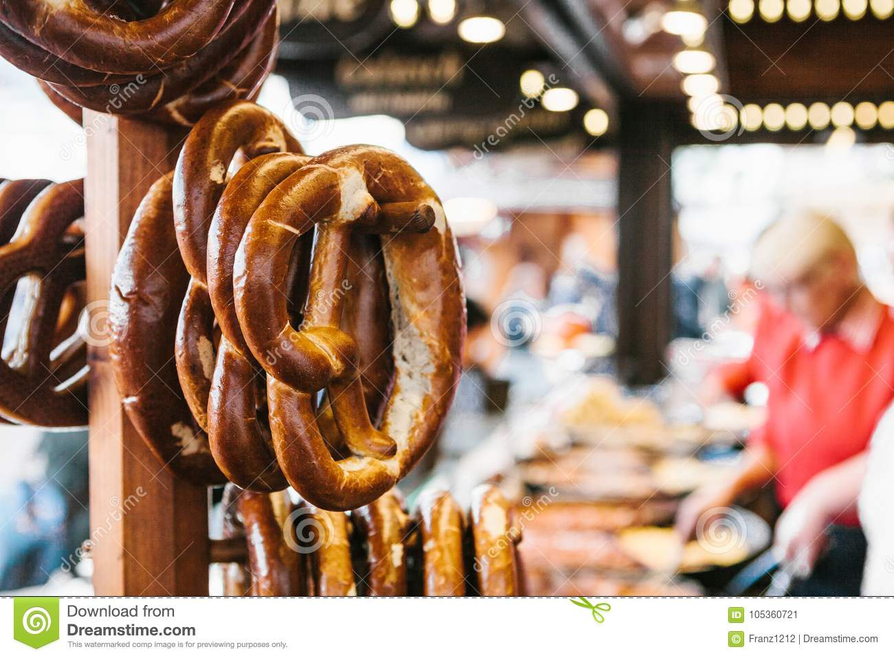 Traditional pretzels called Brezel hang on the stand against the background of a blurred street market and people on