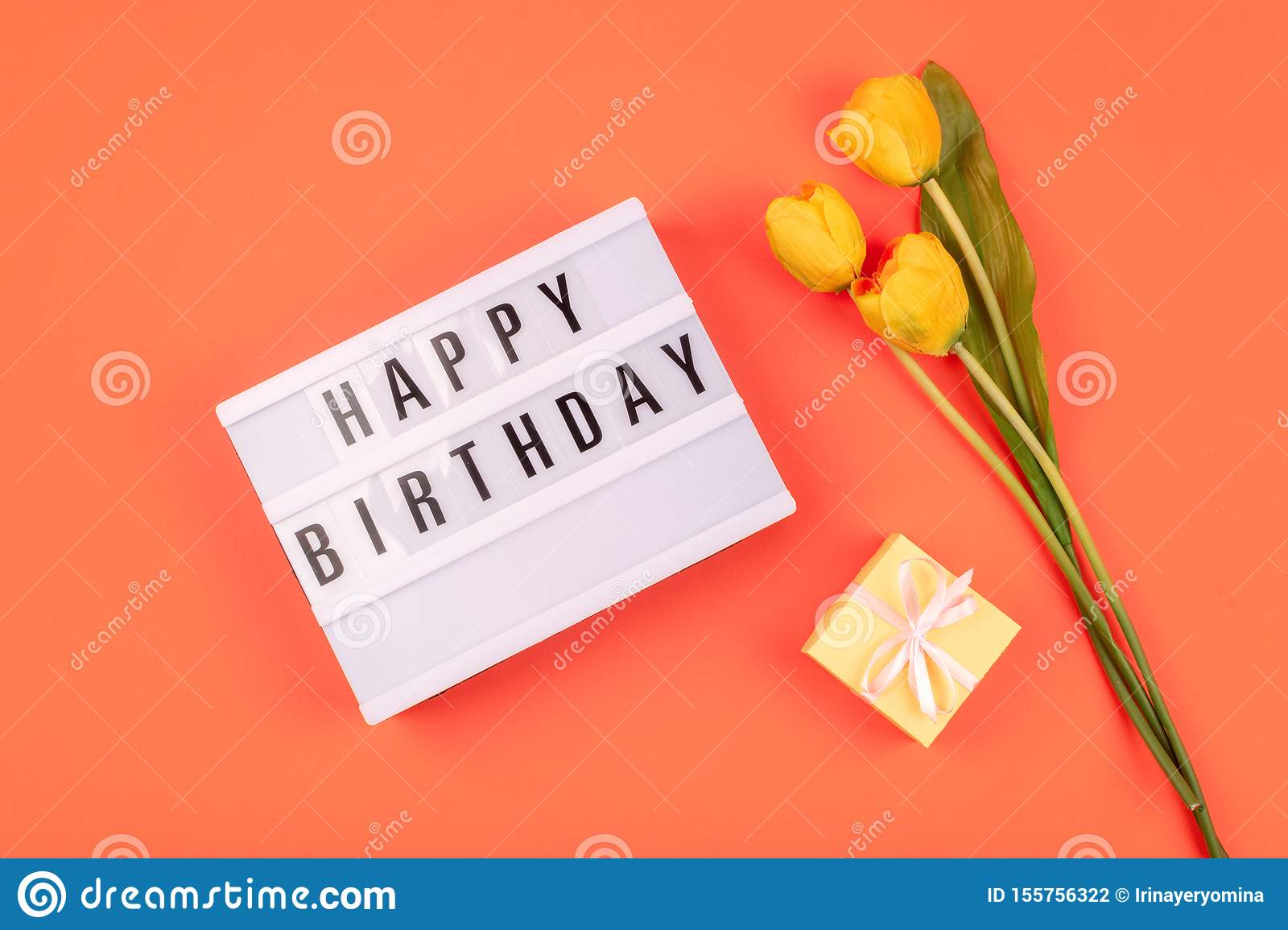 Celebration Happy birthday gift flat lay background. Light box with text Happy birthday and bouquet of yellow tulips on coral