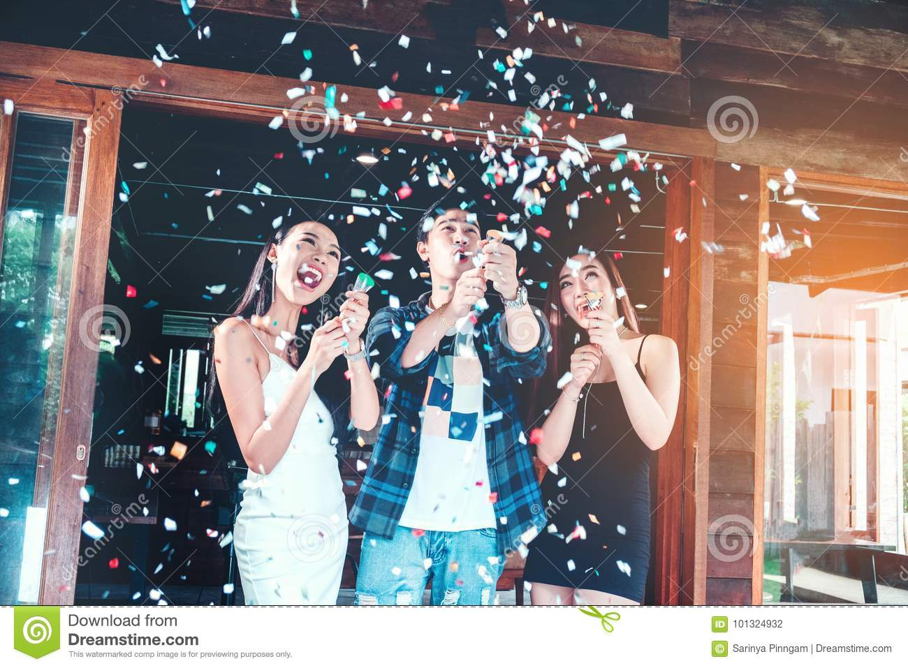 Celebration party group of asian young people holding confetti h