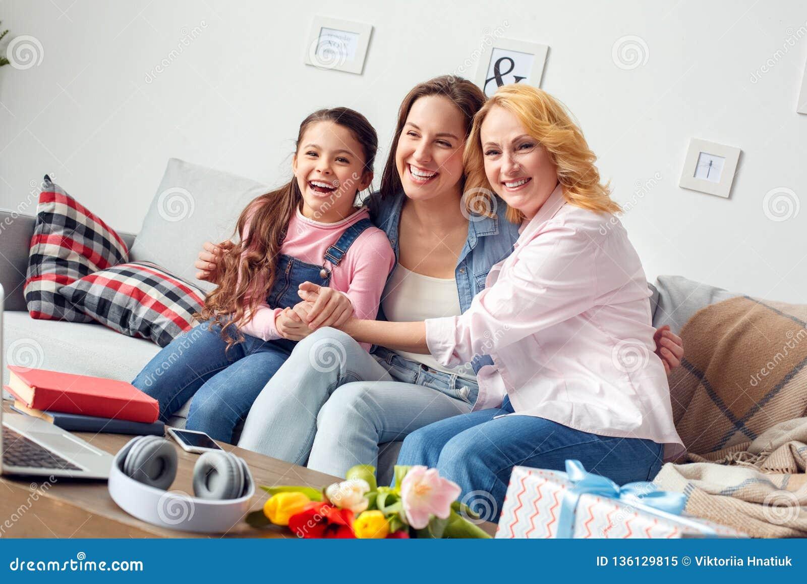 Celebrazione della madre e della figlia della nonna insieme a casa che si siede abbracciando risata allegra